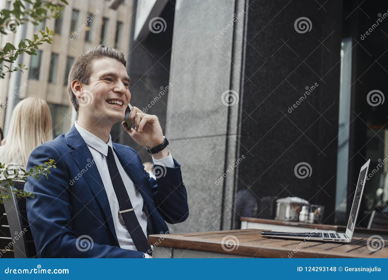 Hombre de negocios moreno atractivo joven que habla el teléfono móvil y sonriendo