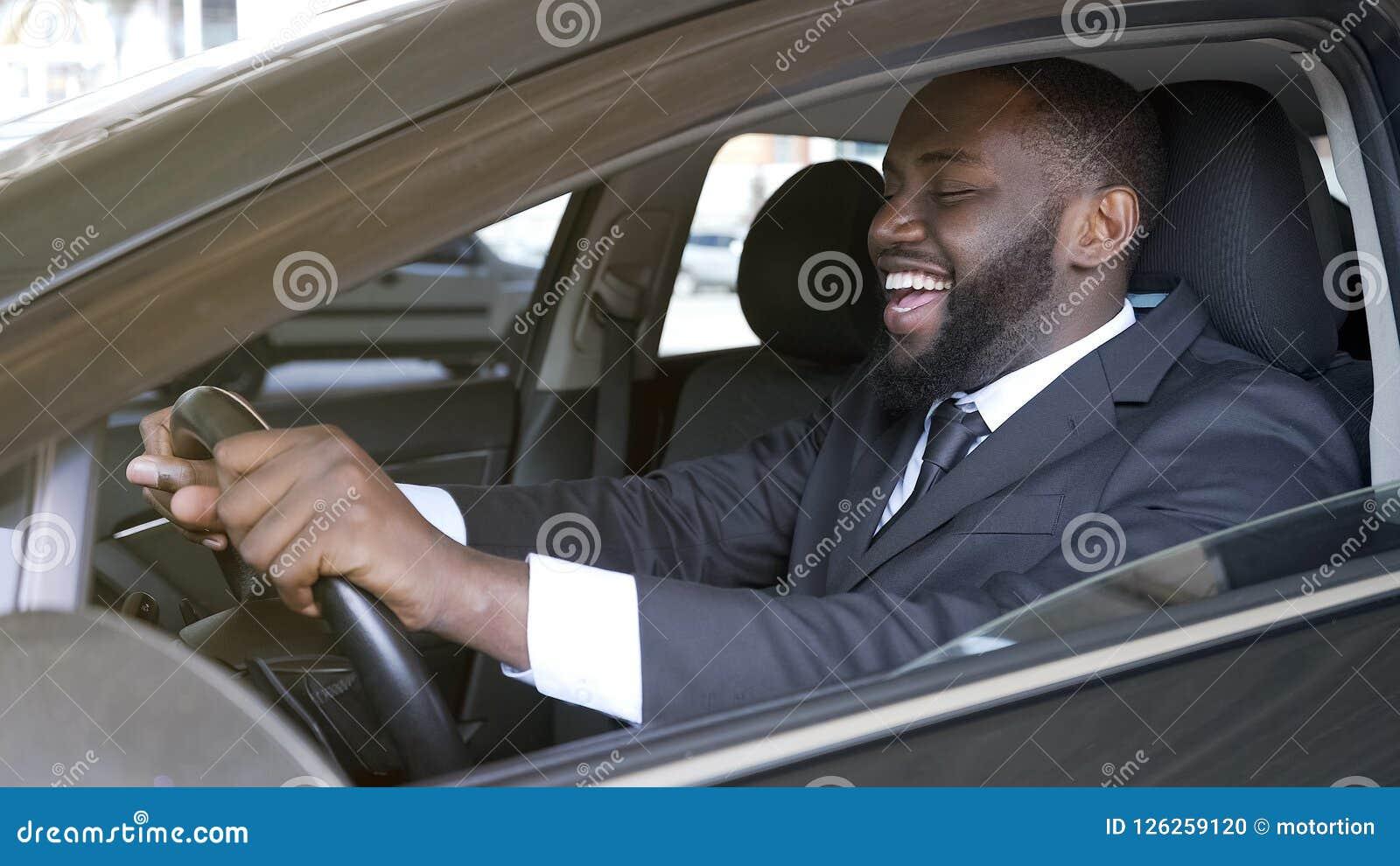 Hombre de negocios negro alegre que se sienta en el automóvil de lujo, prueba de conducción, transporte
