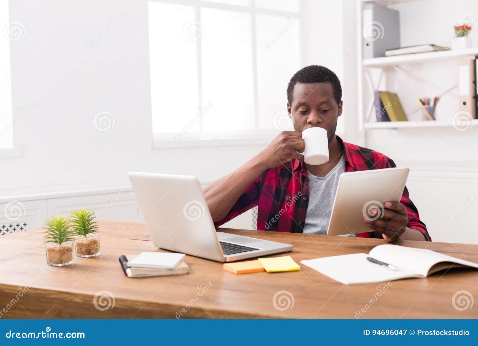 Hombre de negocios negro en oficina casual, leyendo noticias en la tableta, café de consumición