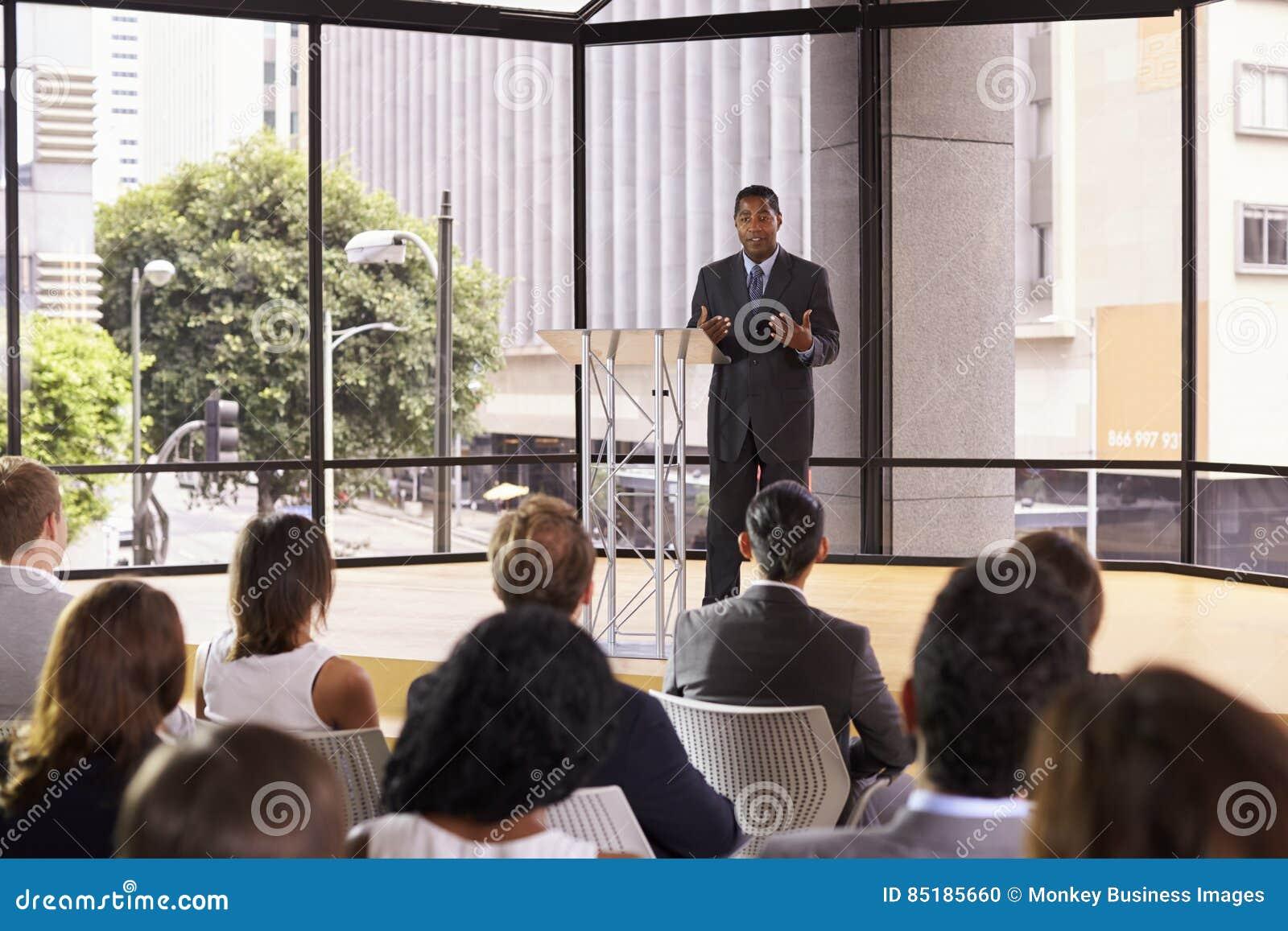 Hombre de negocios negro que presenta el seminario que gesticula a la audiencia