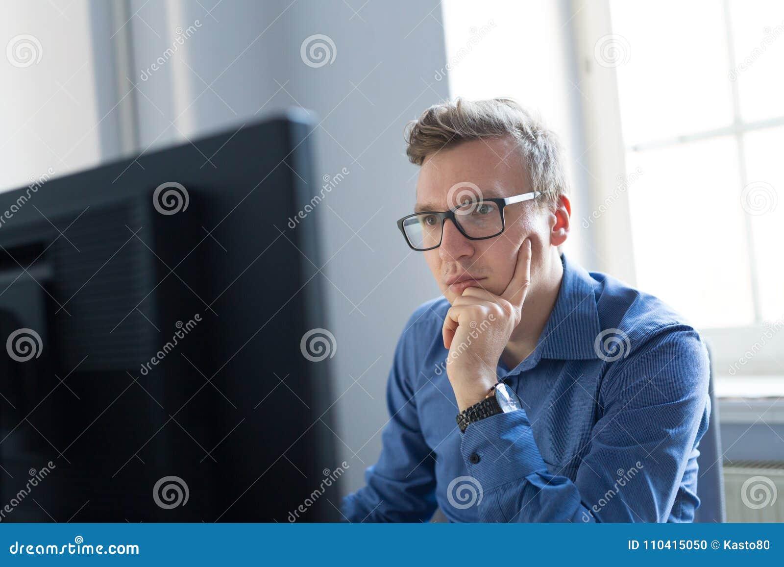 Hombre de negocios ocasional que trabaja en oficina, sentándose en el escritorio, pulsando en el teclado, mirando la pantalla de