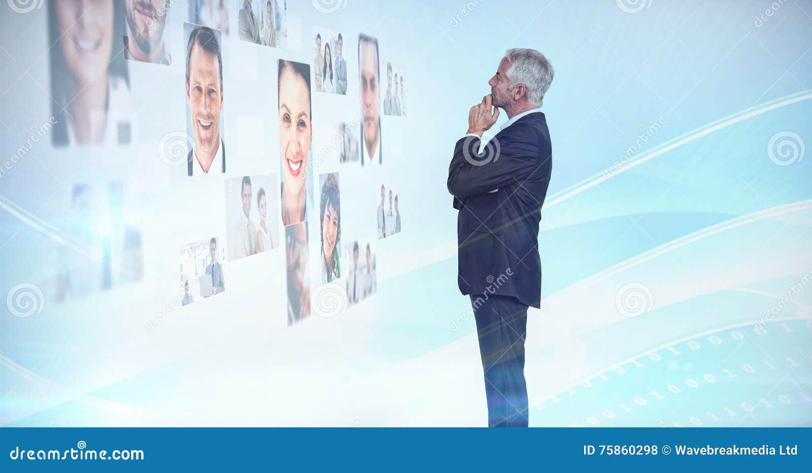 Hombre de negocios pensativo que mira una pared cubierta por las imágenes del perfil