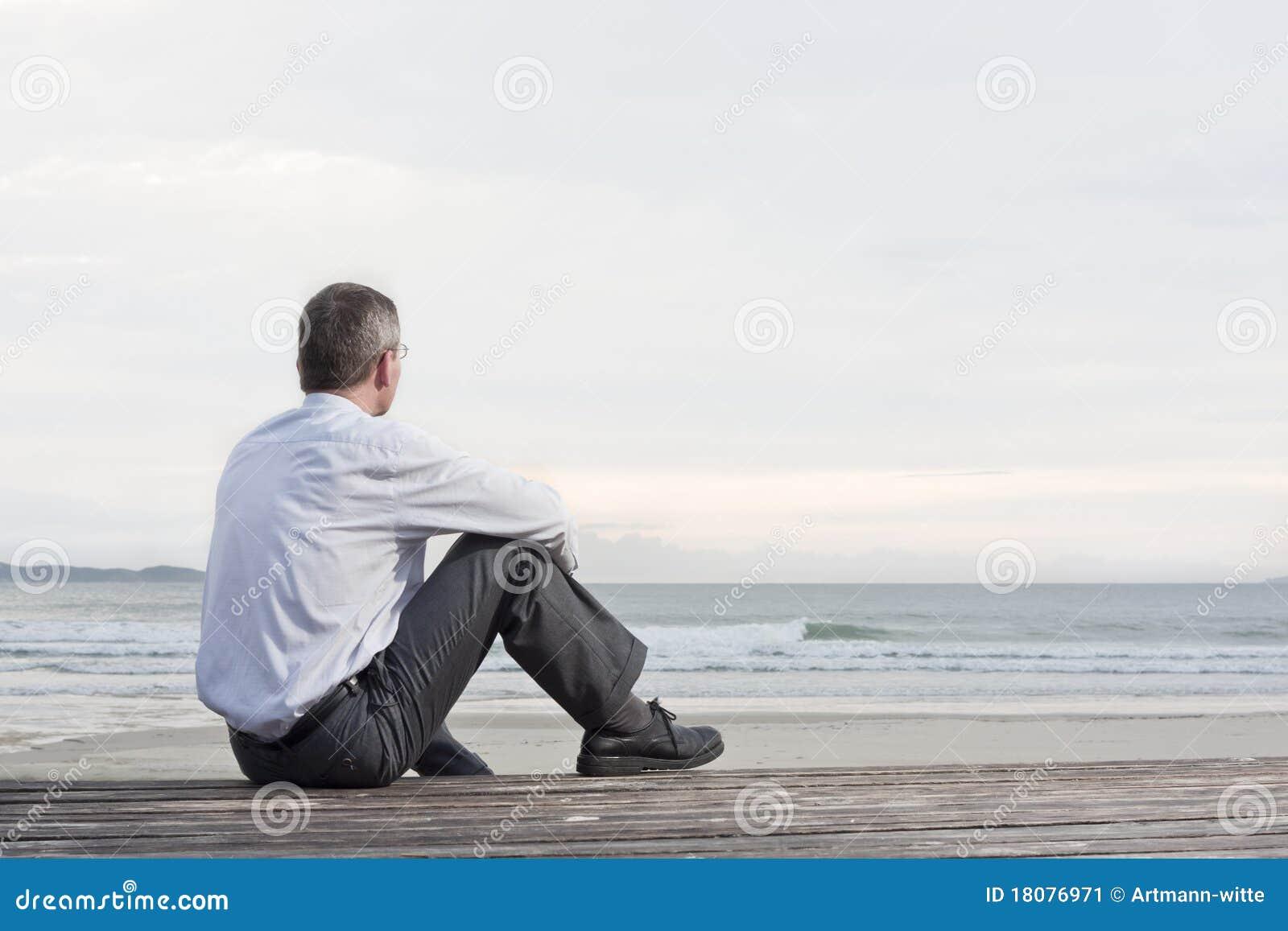 Hombre de negocios pensativo que se sienta en el mar