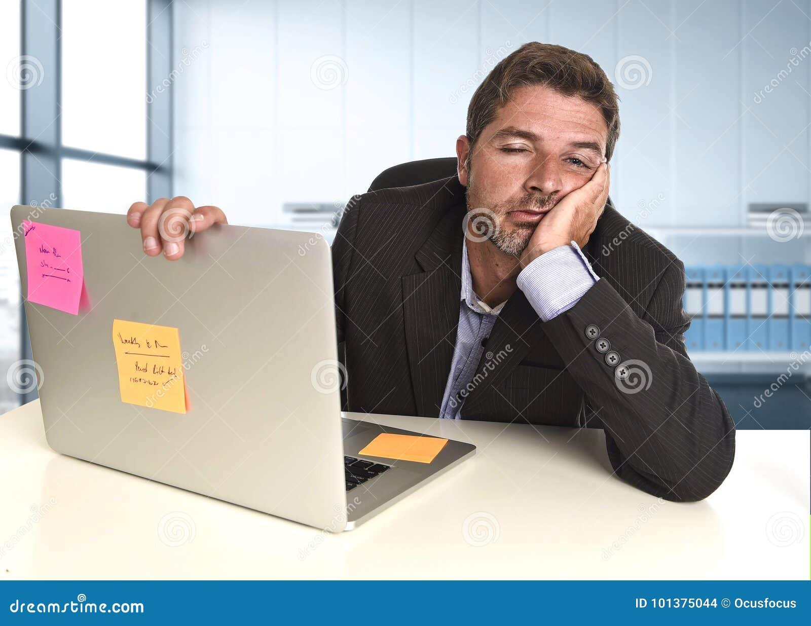 Hombre de negocios perdido que trabaja en la tensión en el ordenador portátil de la oficina que parece agotado