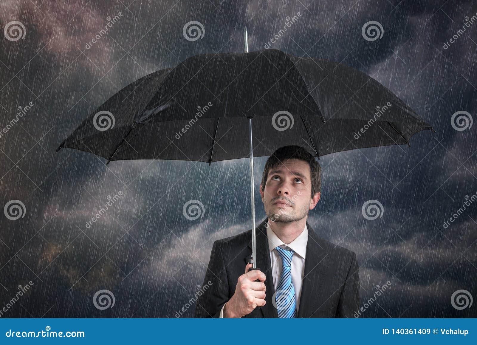 Hombre de negocios pesimista con el paraguas negro en tormenta