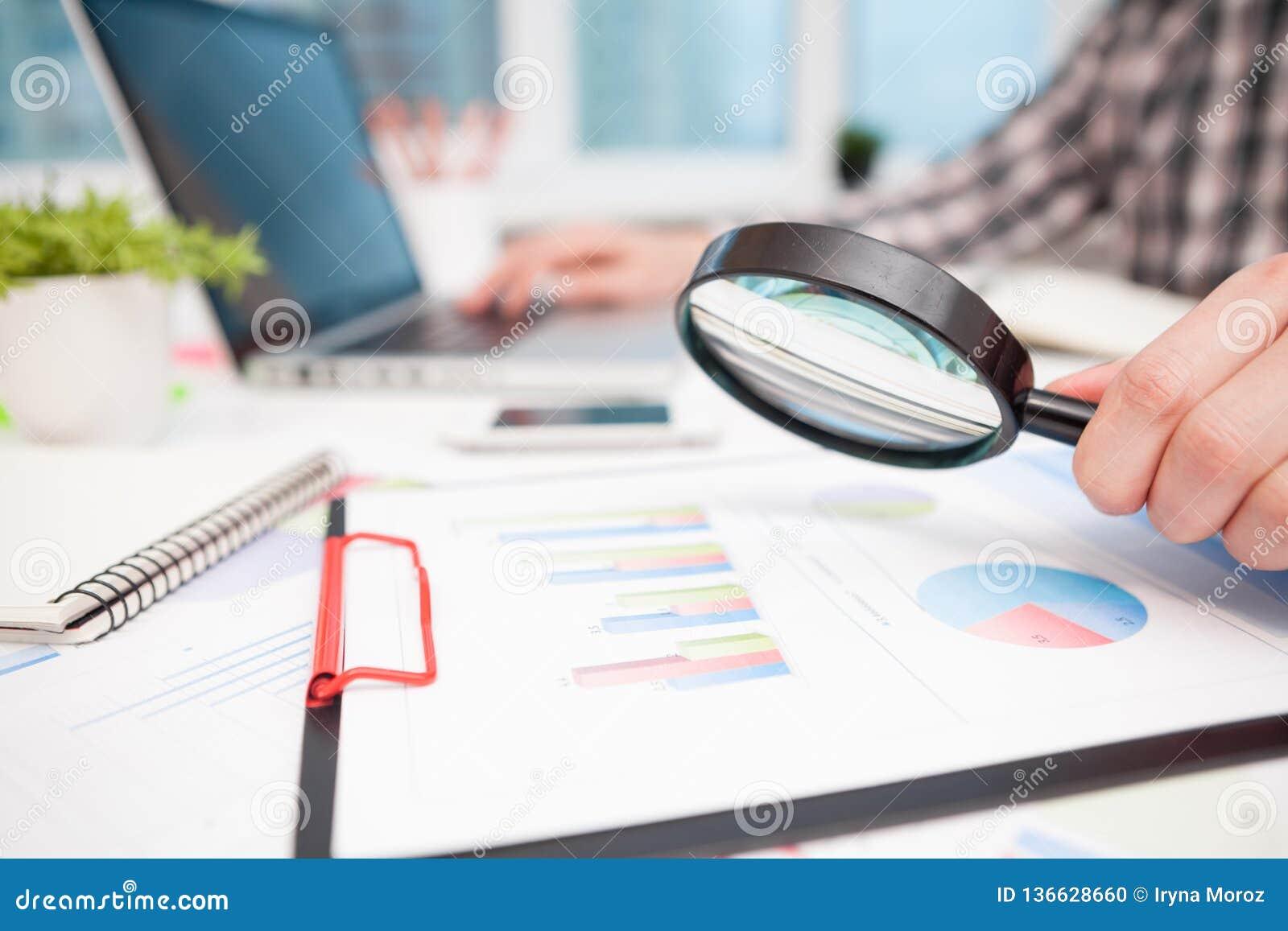 Hombre de negocios que analiza gráficos de negocio con la lupa