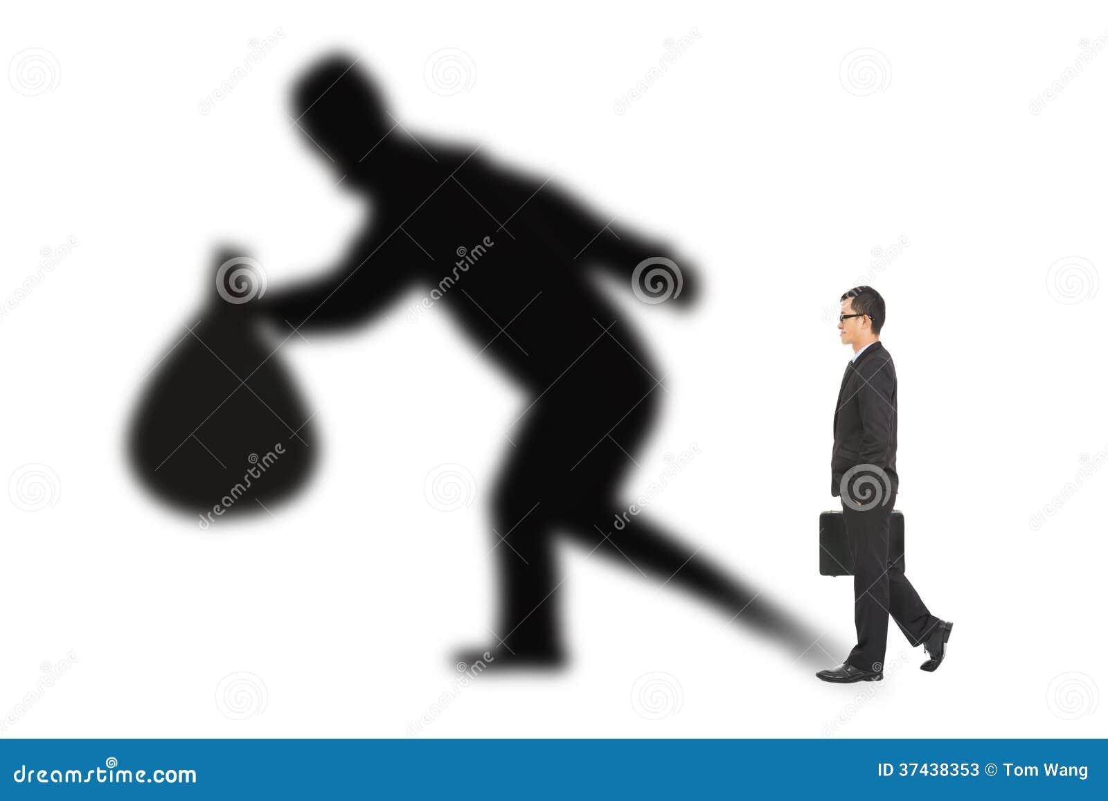 Hombre de negocios que camina y que sostiene el bolso con la sombra del ladrón