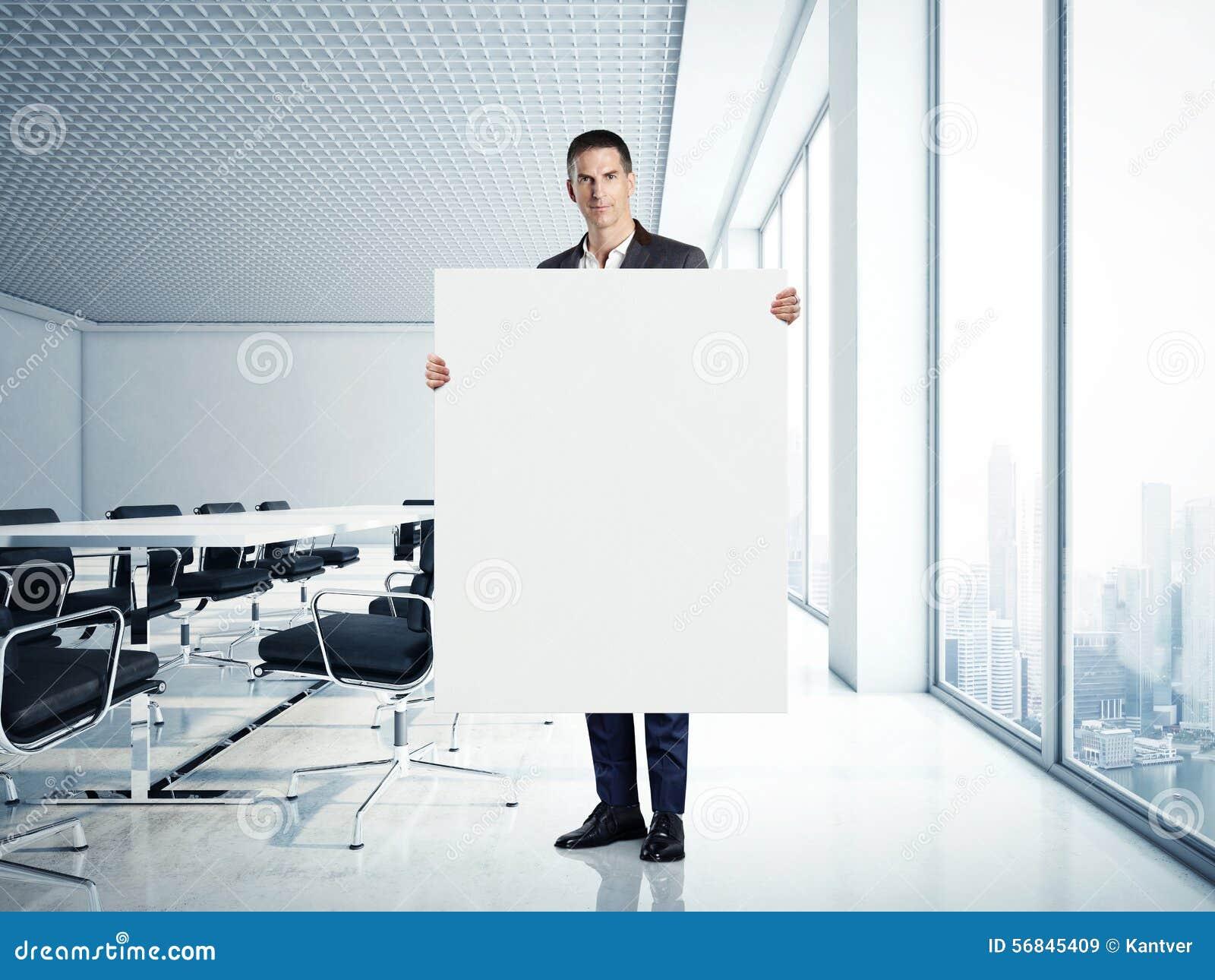 Hombre de negocios que celebra la lona en la oficina moderna