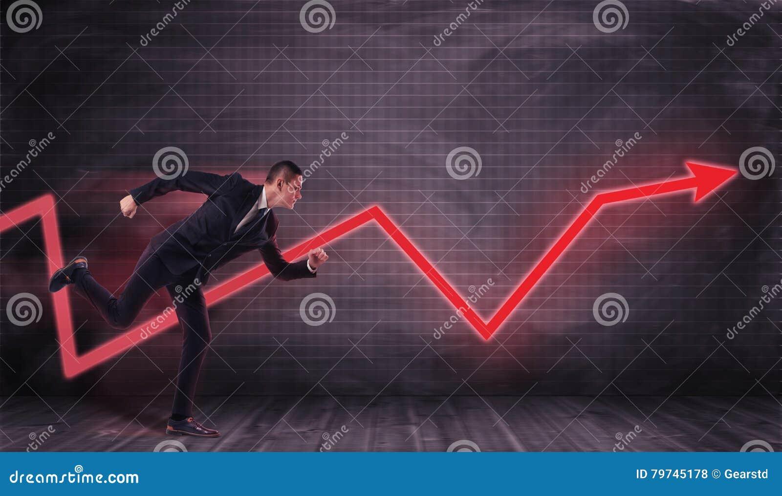 Hombre de negocios que corre en dirección de la flecha roja que intenta alcanzarla