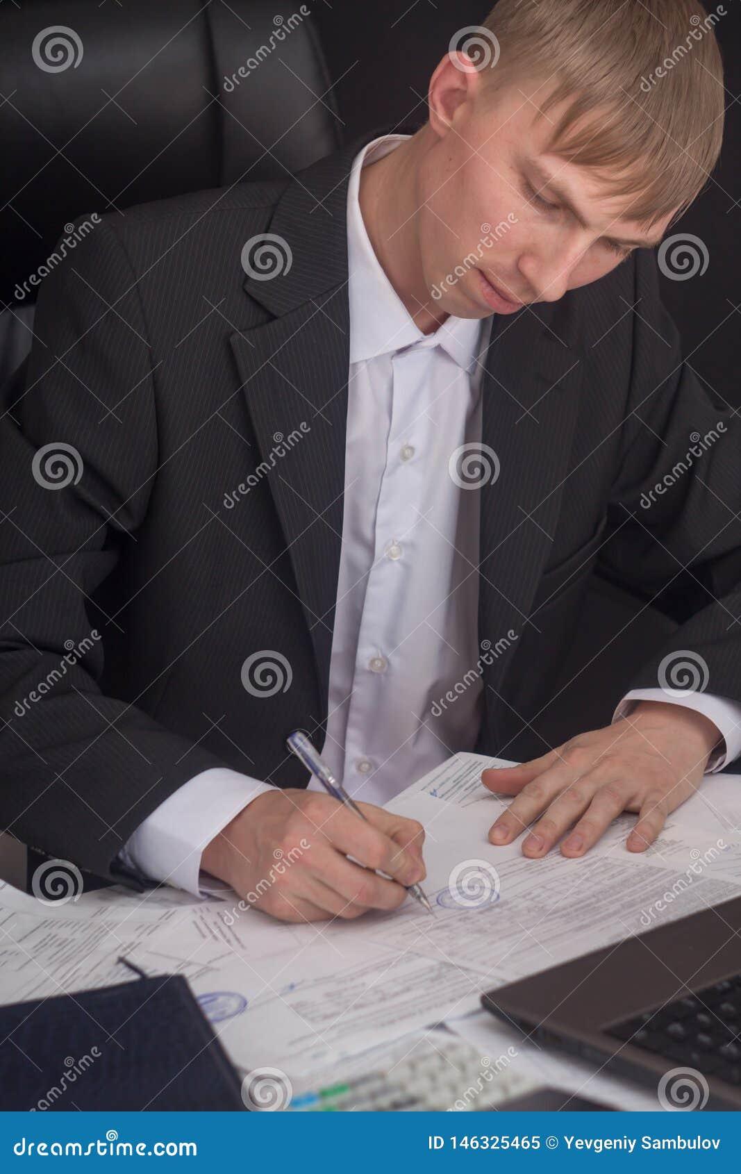 Hombre de negocios que firma un contrato El encargado hace el informe y completa la declaraci?n Hombre de negocios en el trabajo