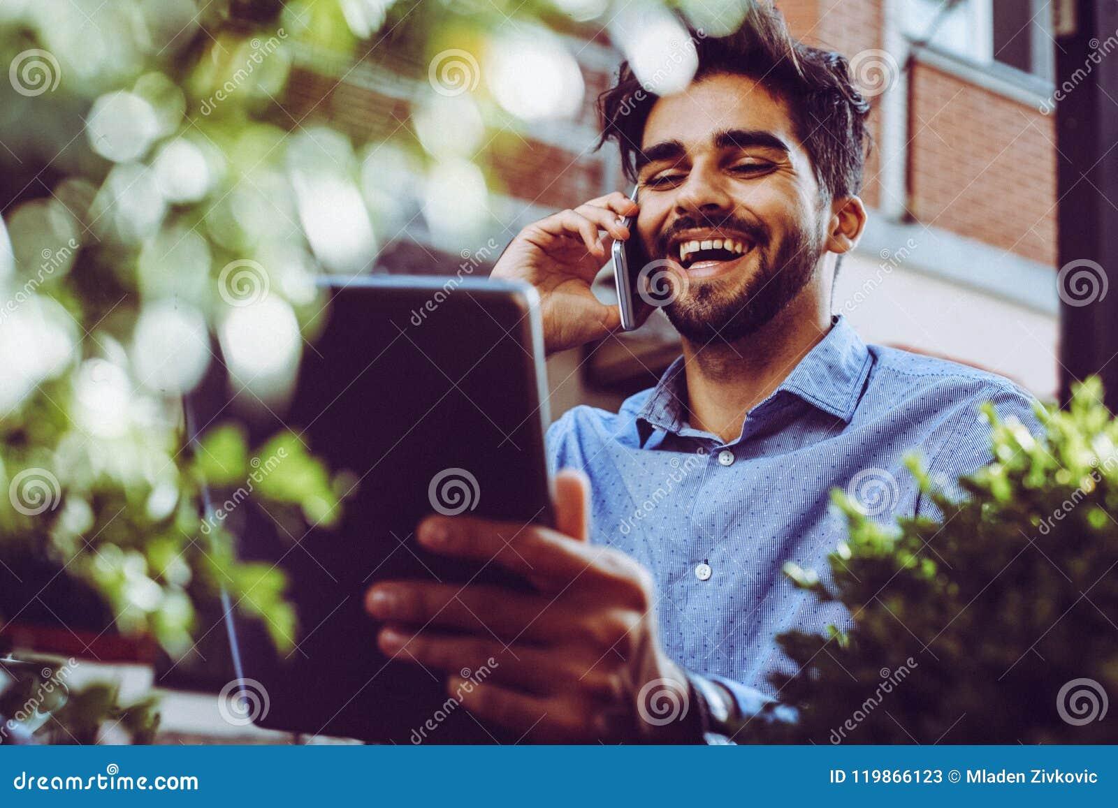Hombre de negocios que habla en el teléfono elegante y que usa la tableta digital