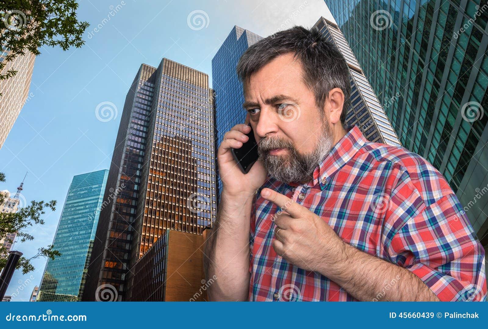 Hombre de negocios que habla en el teléfono móvil en la megalópoli