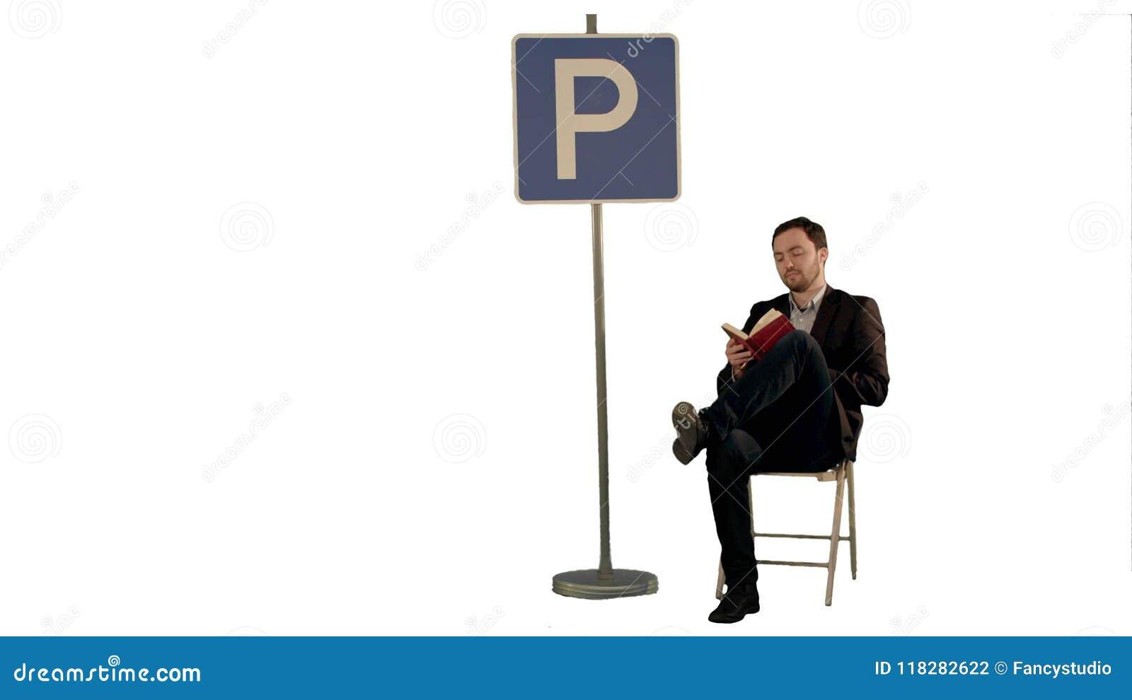 Hombre de negocios que lee un libro cerca de muestra del estacionamiento en el fondo blanco aislado