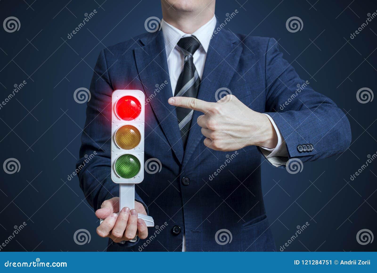 Hombre de negocios que lleva a cabo un semáforo con la luz roja encendido