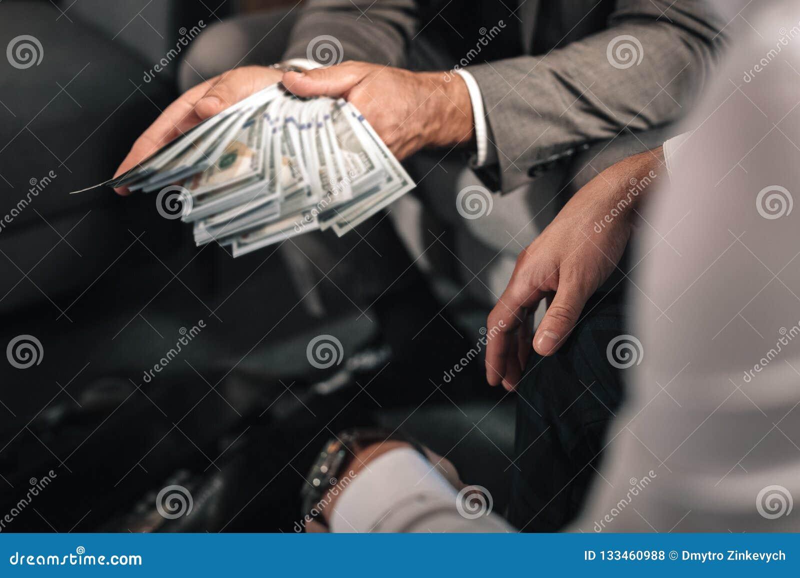 Hombre de negocios que lleva la chaqueta gris oscuro que da el soborno al abogado