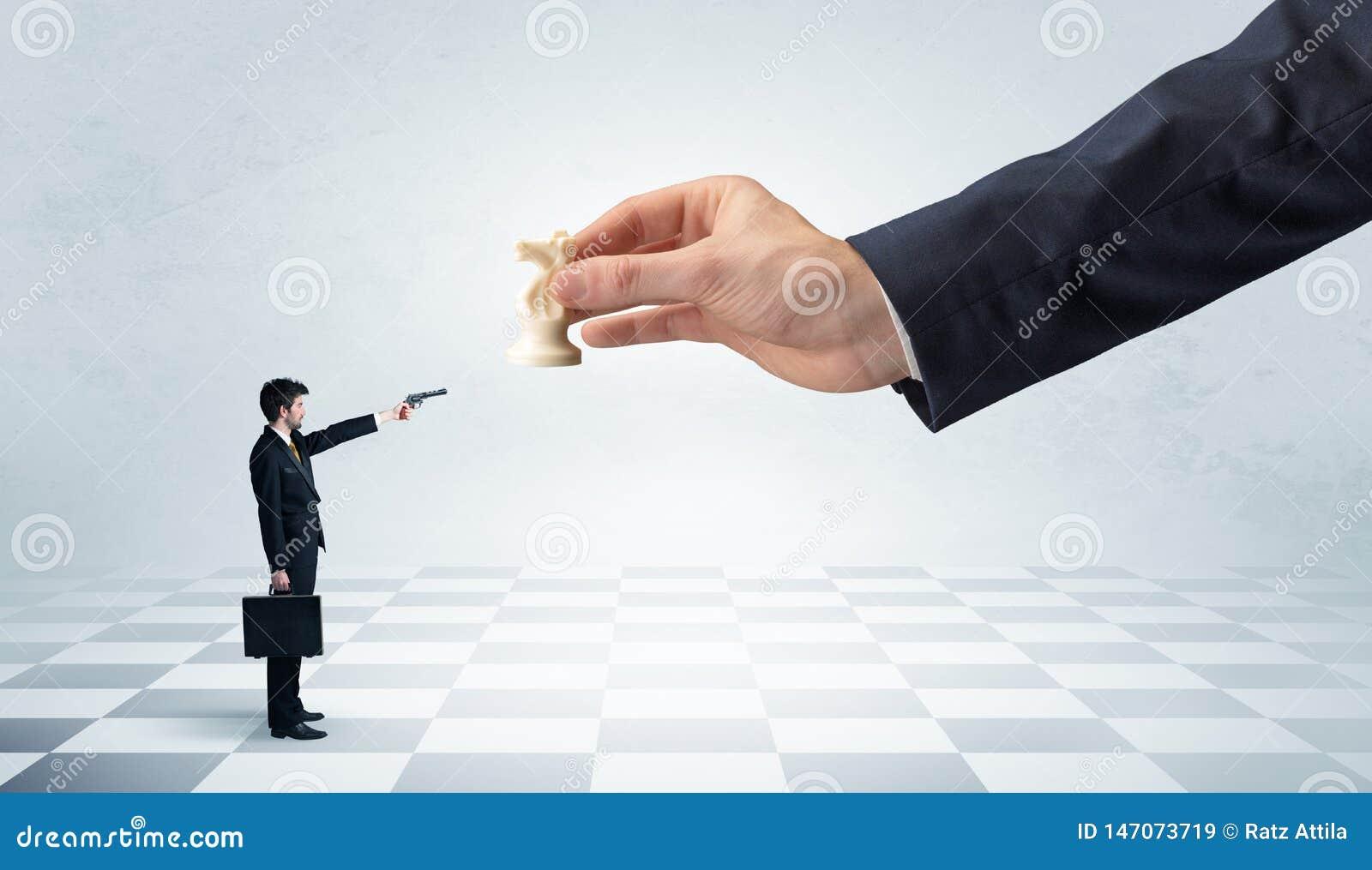 Hombre de negocios que lucha contra la pieza de ajedrez grande en una mano grande