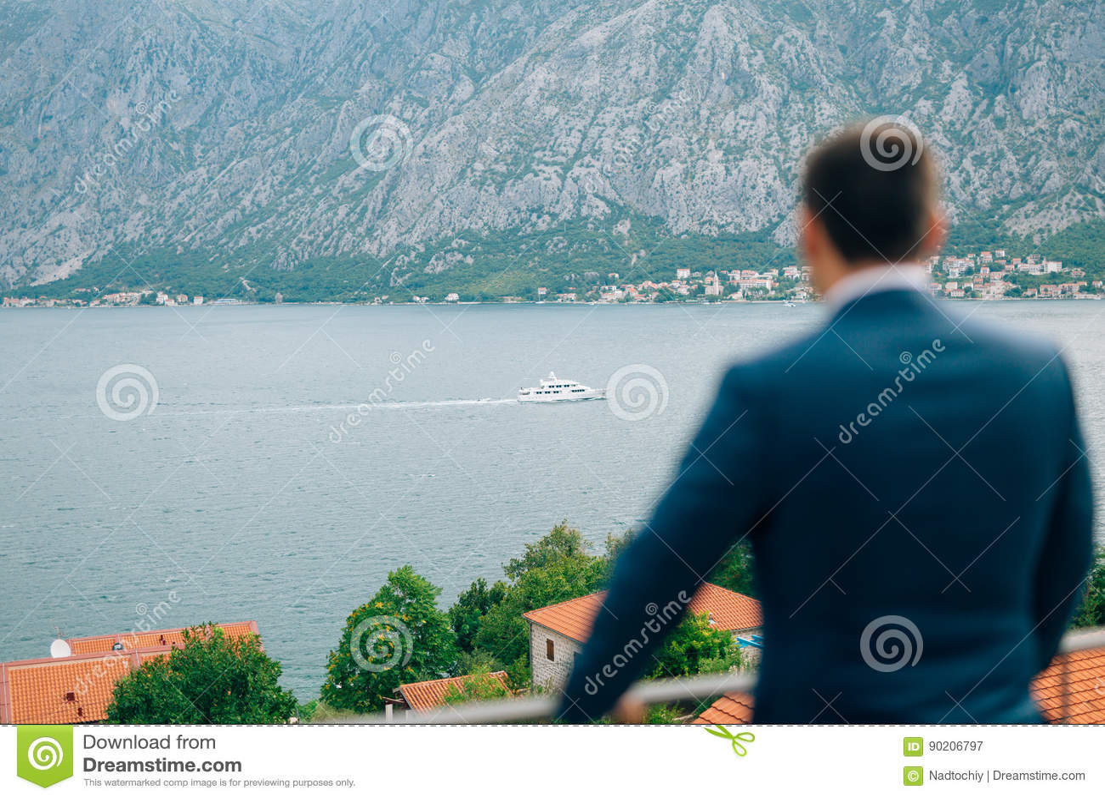 Hombre de negocios que mira al yate Bahía de Kotor, la ciudad de Prca