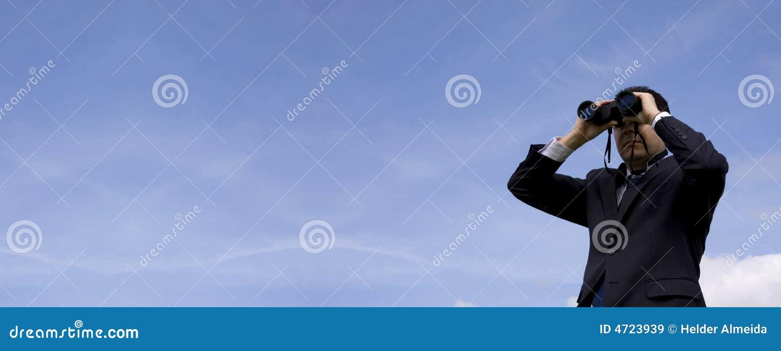 Hombre de negocios que mira a través de los prismáticos