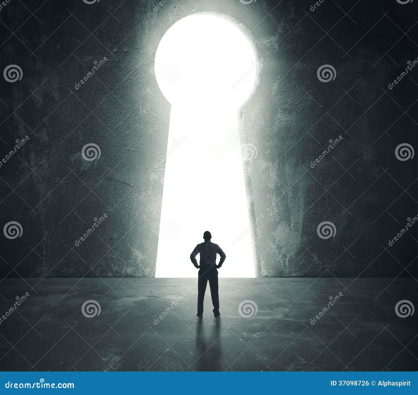 Hombre de negocios que mira a través del agujero de la cerradura