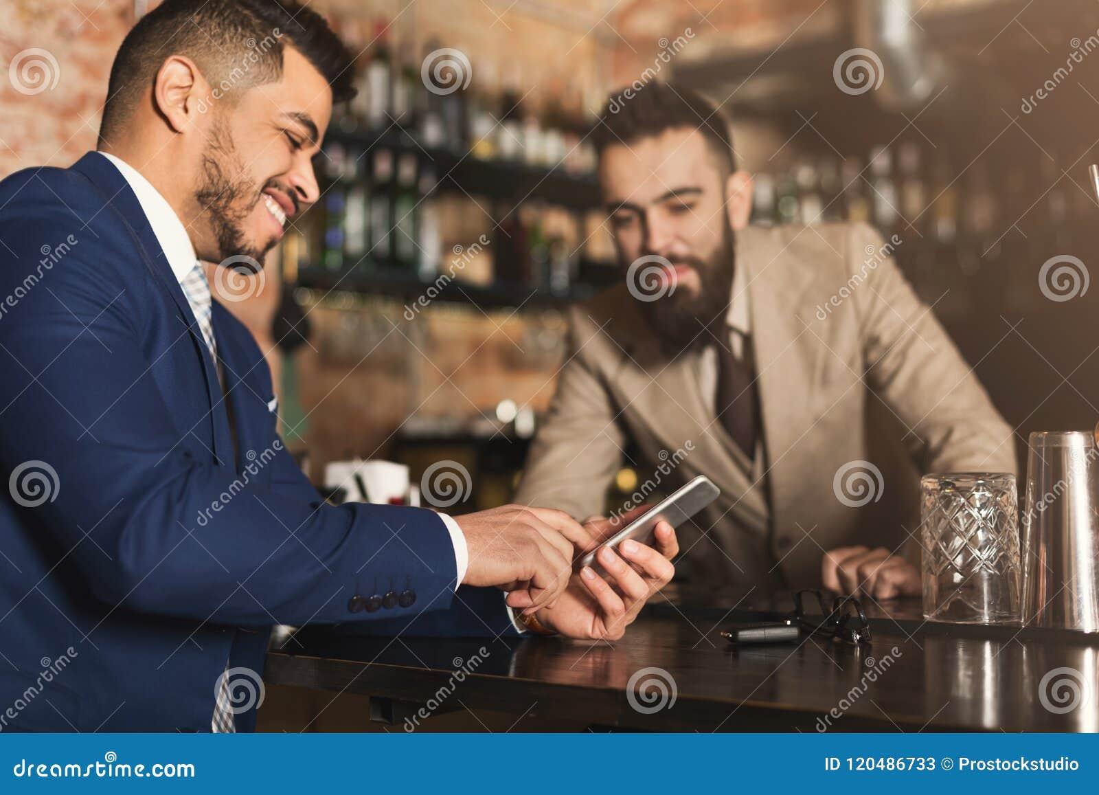 Hombre de negocios que muestra la información sobre el teléfono al camarero