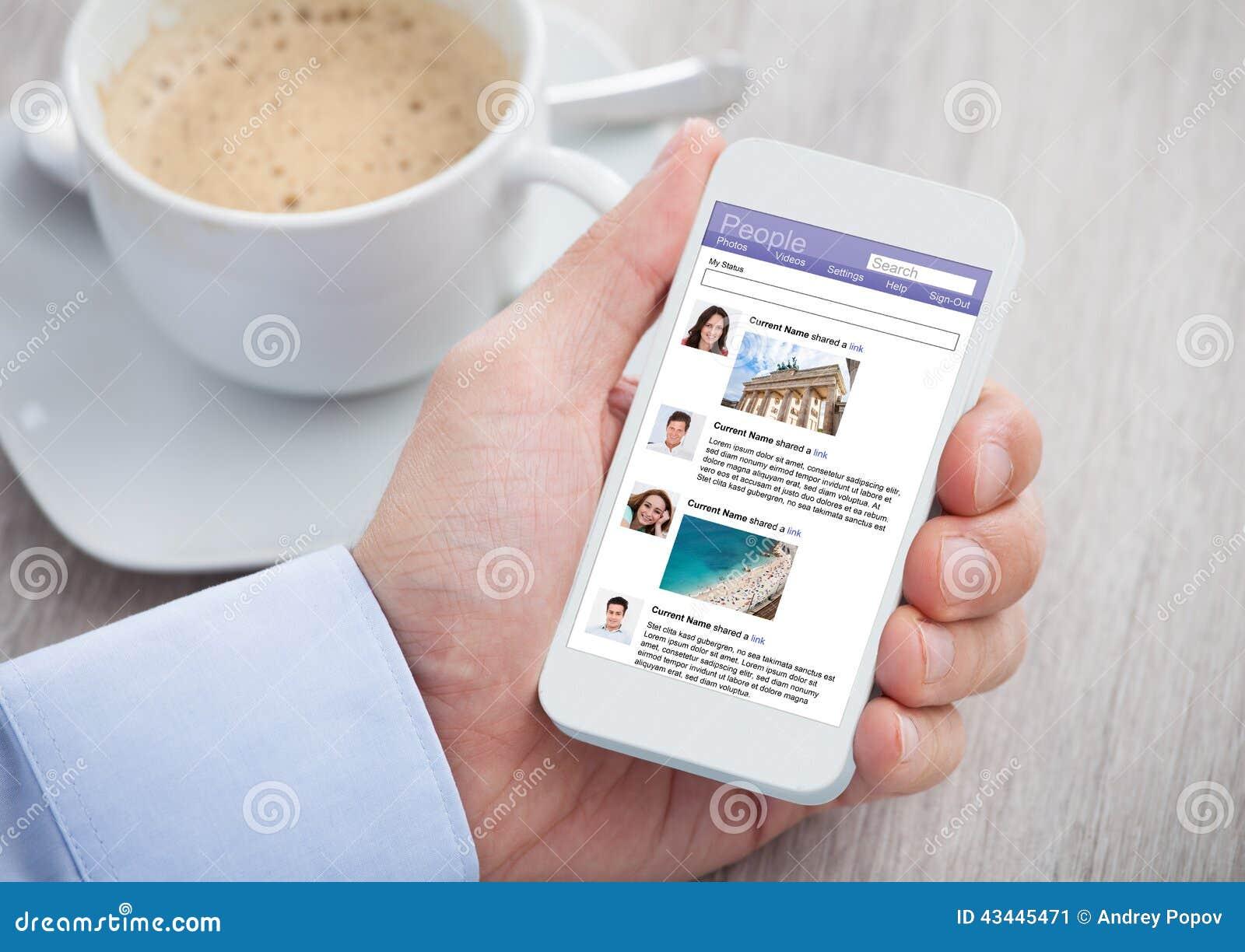 Hombre de negocios que practica surf el sitio social del establecimiento de una red en el móvil