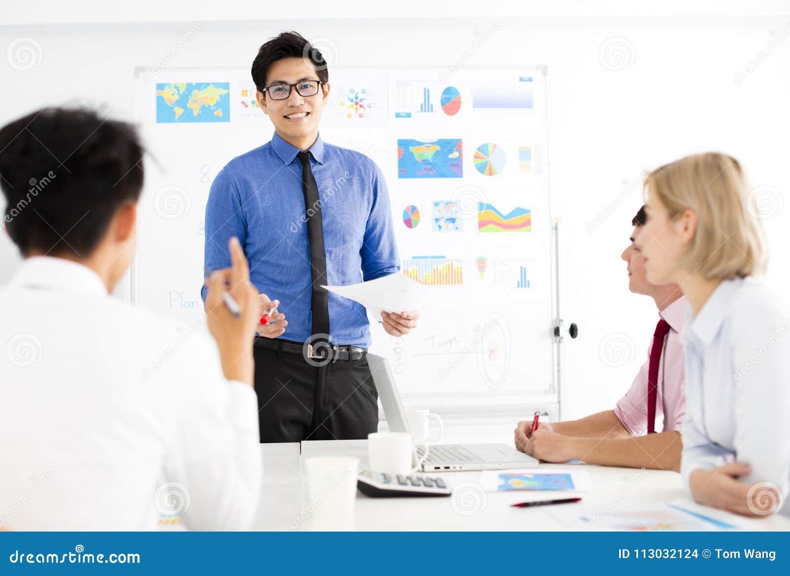 Hombre de negocios que presenta a los colegas en la reunión