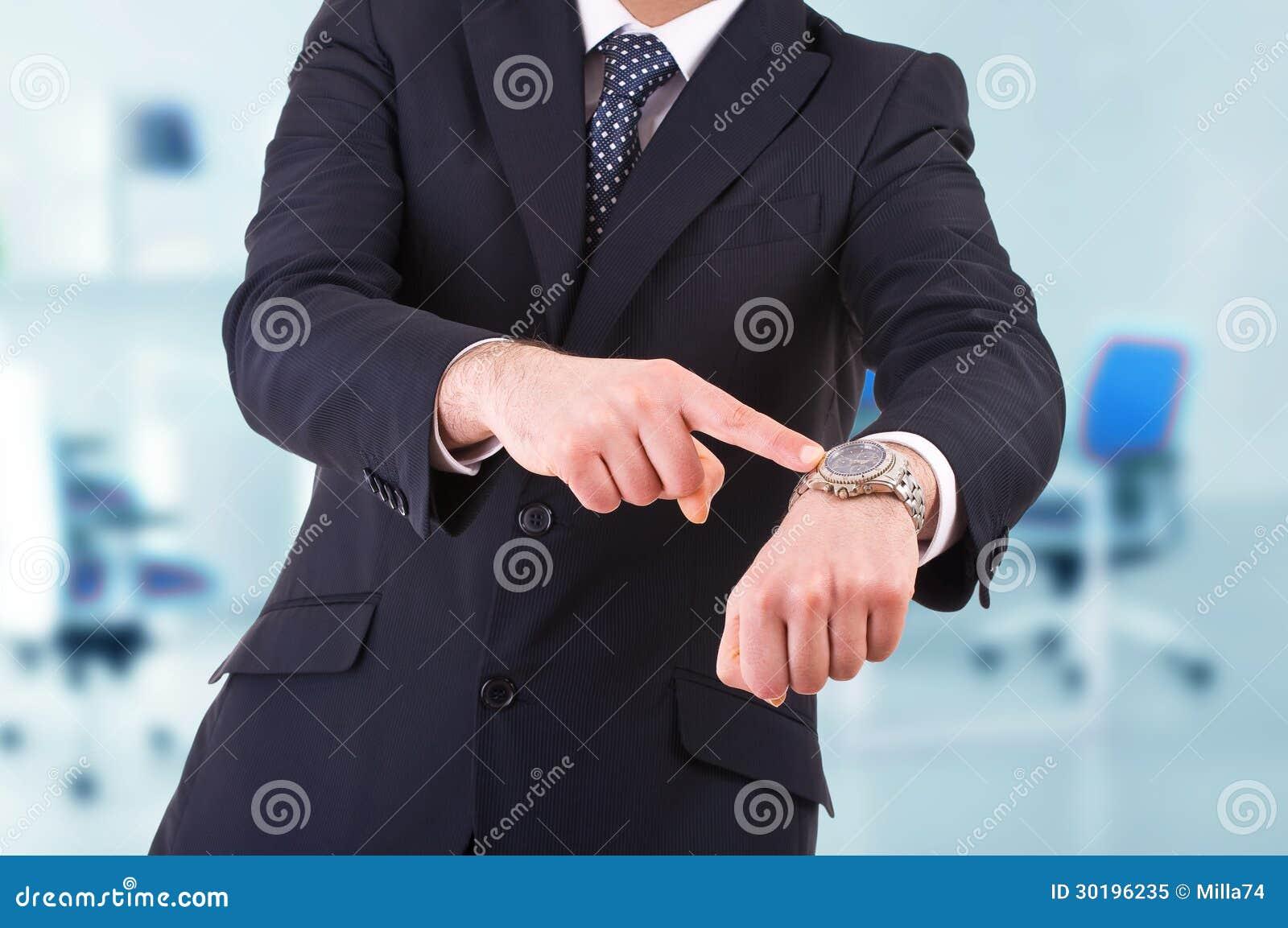 Hombre de negocios que señala en su reloj.