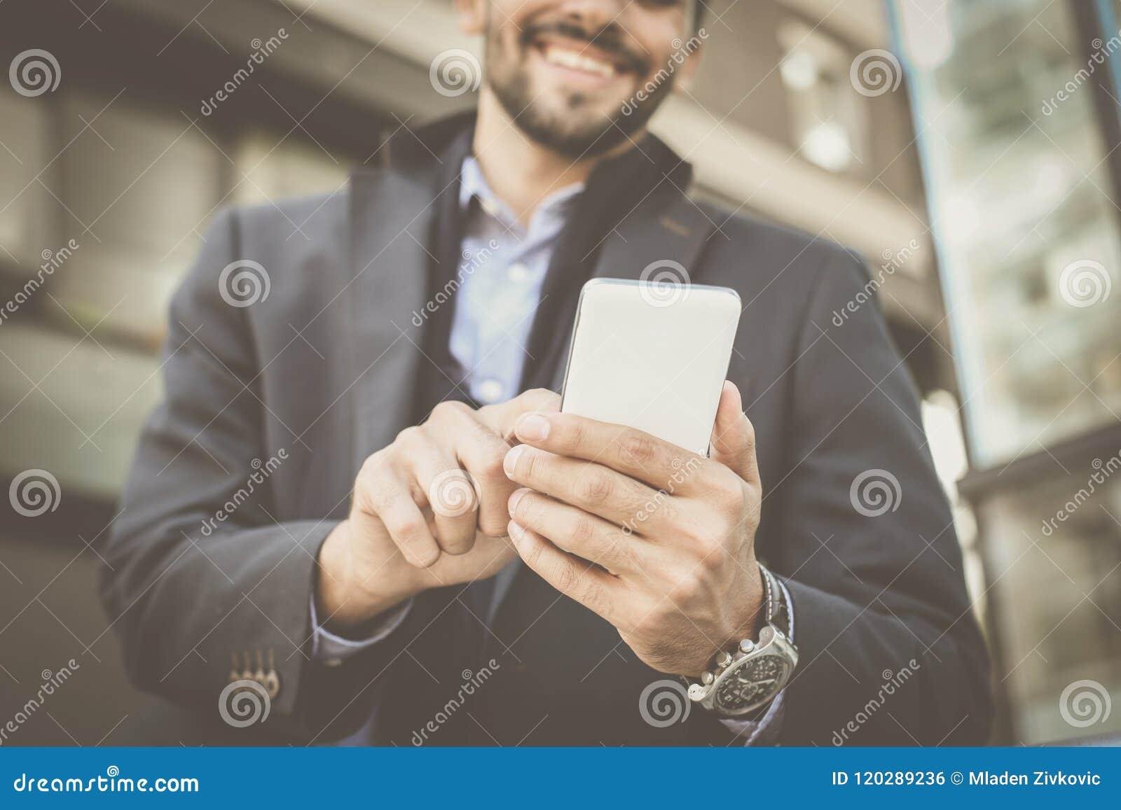 Hombre de negocios que se coloca en la calle de la ciudad y que lleva a cabo phon elegante