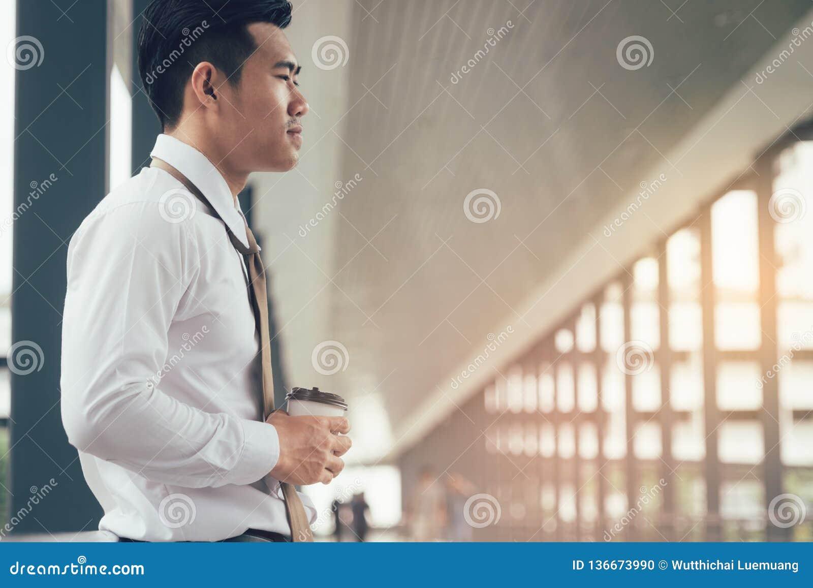 Hombre de negocios que se coloca en la compañía de la calzada del edificio con concepto de la esperanza