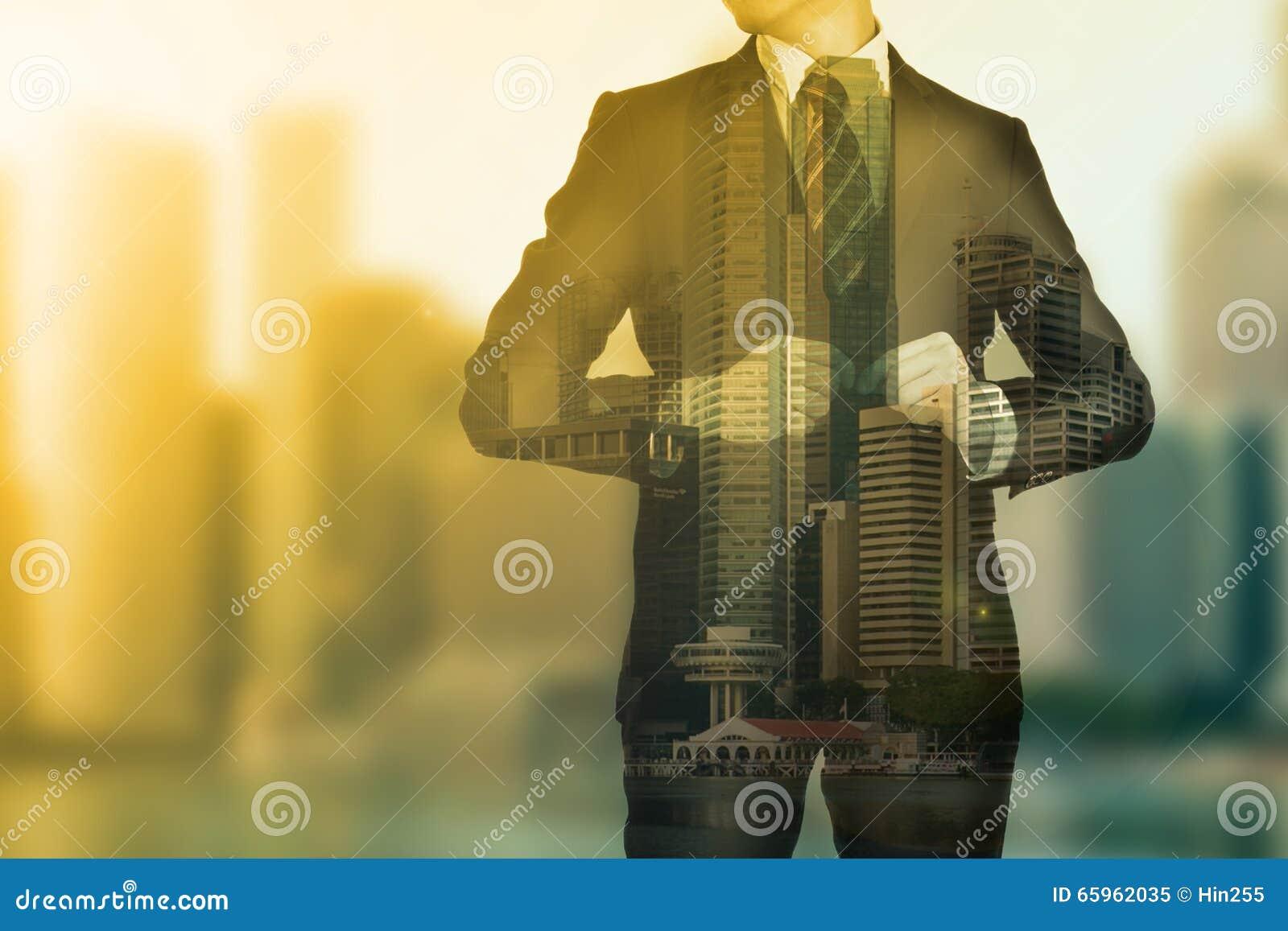 Hombre de negocios que se coloca para mirar su negocio del éxito