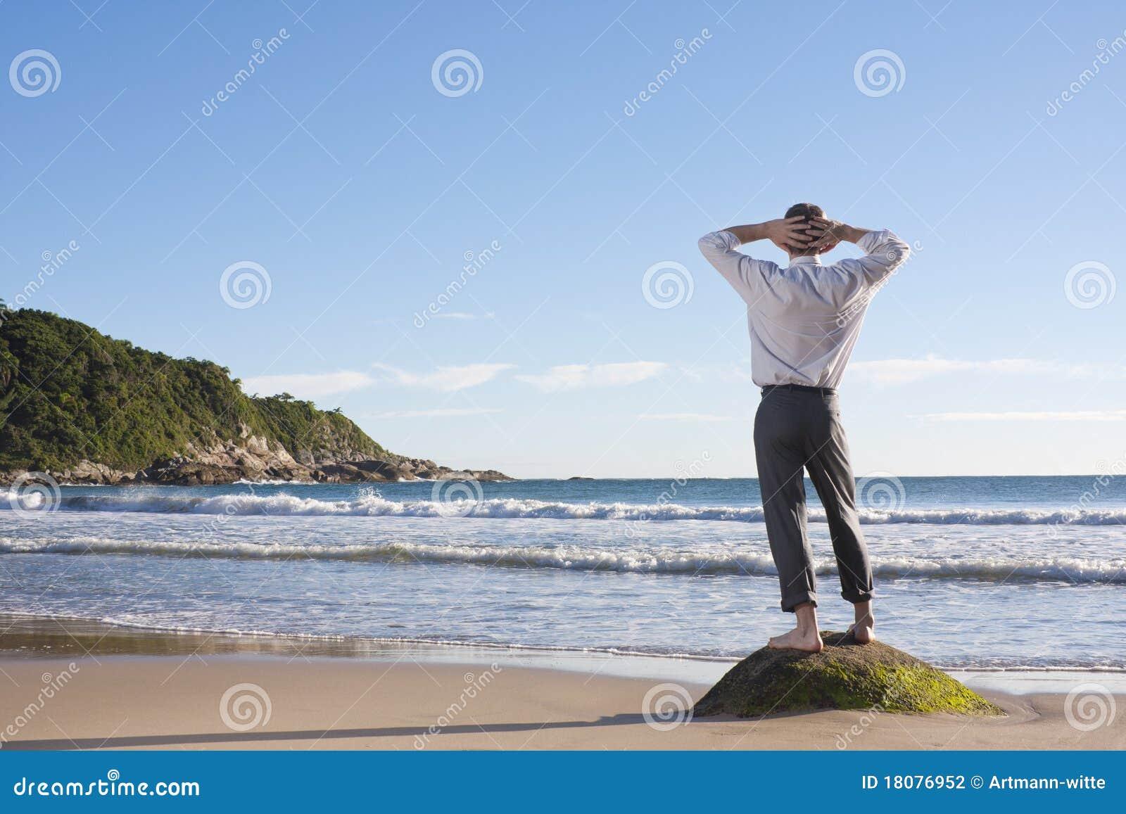 Hombre de negocios que se relaja en una playa
