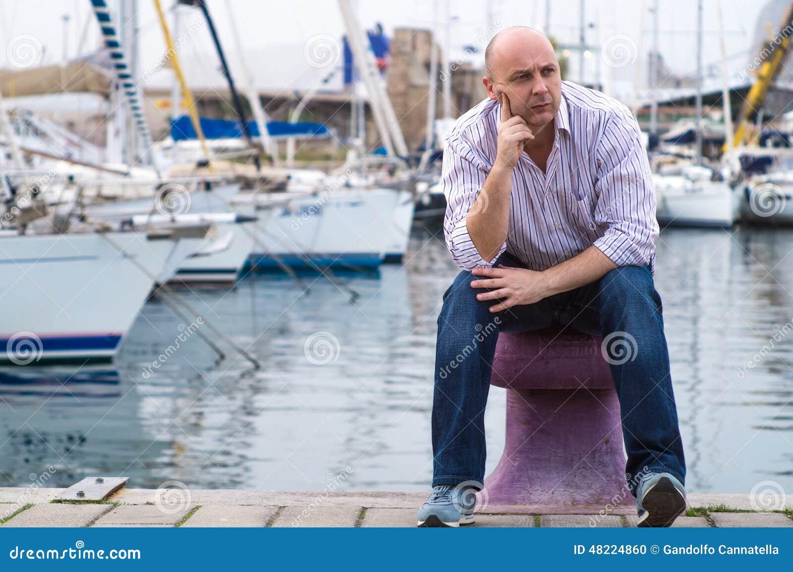 Hombre de negocios que se sienta en barcos y yates costosos de navegación en el A.C.