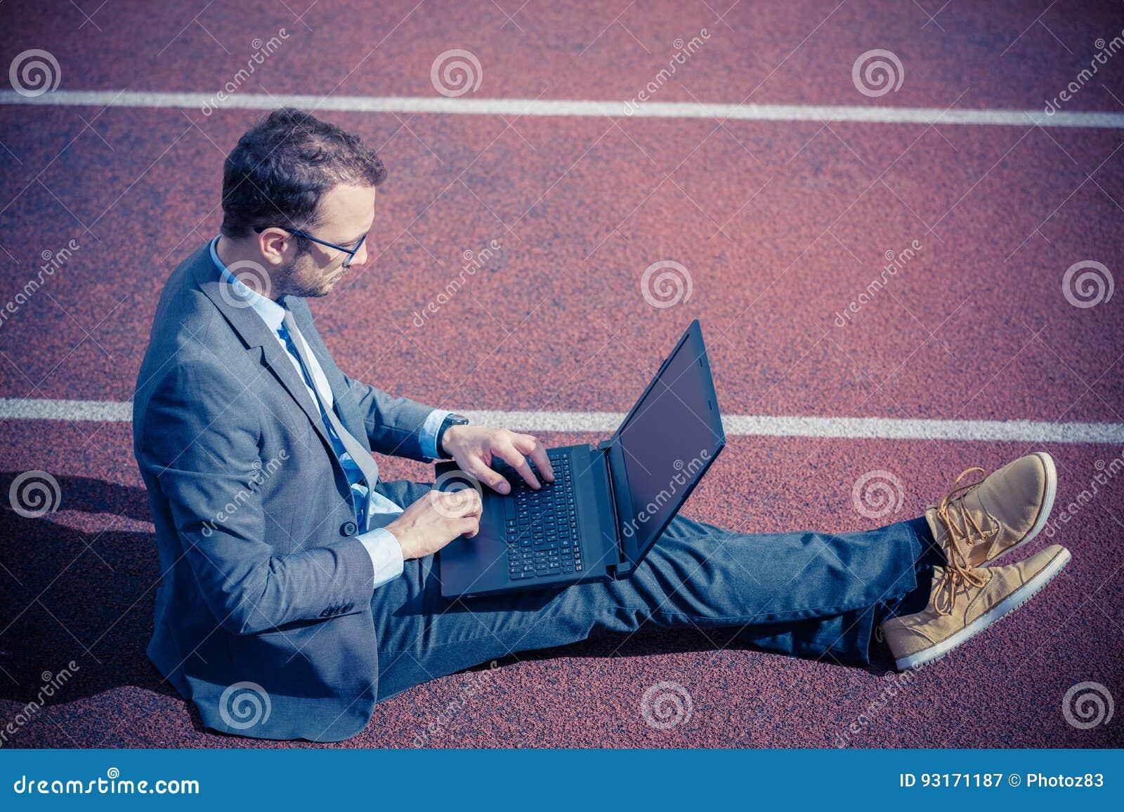 Hombre de negocios que se sienta en pista que compite con y que trabaja en el ordenador portátil