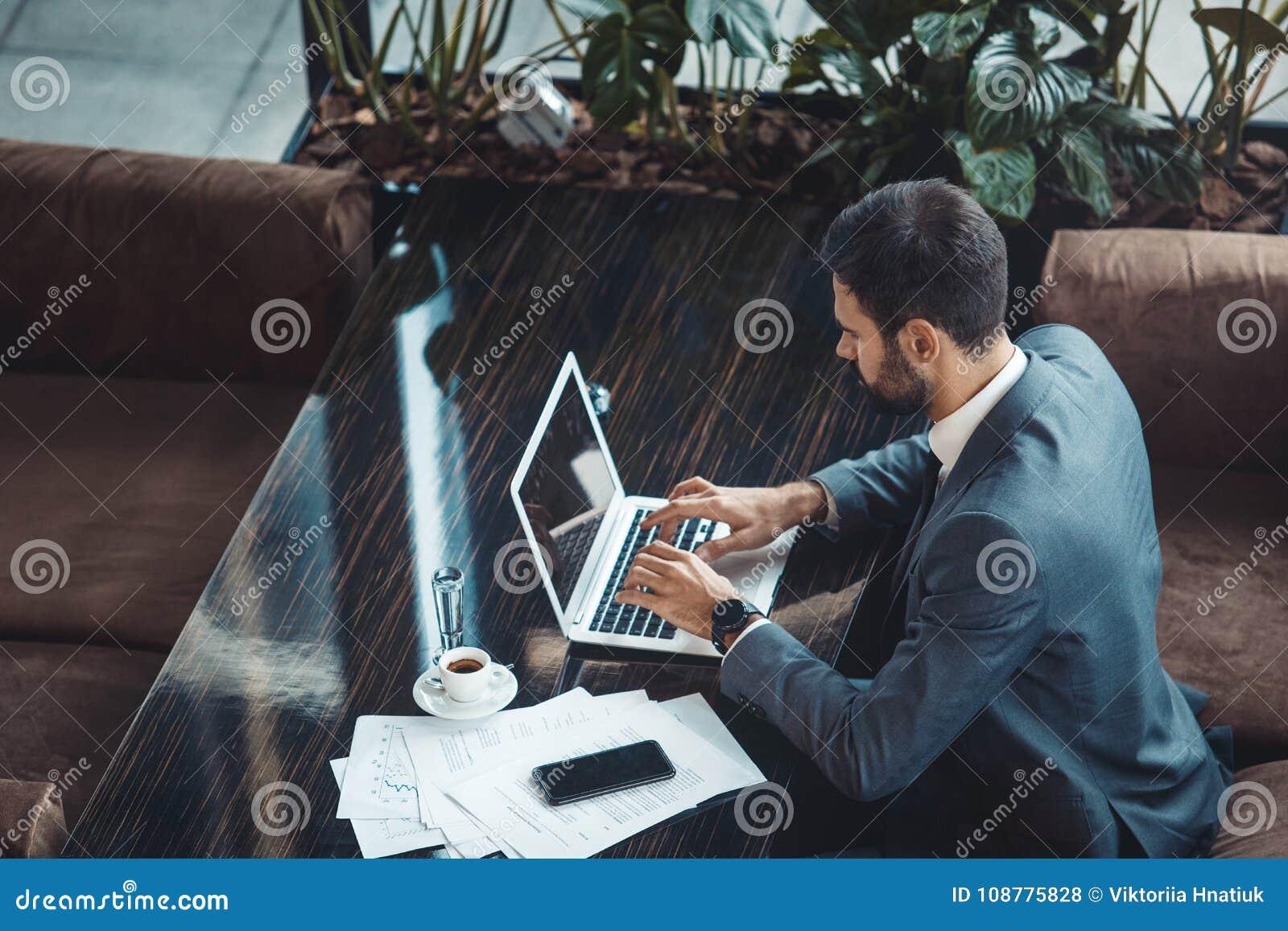 Hombre de negocios que se sienta en un restaurante del centro de negocios que mecanografía en la opinión superior del ordenador p