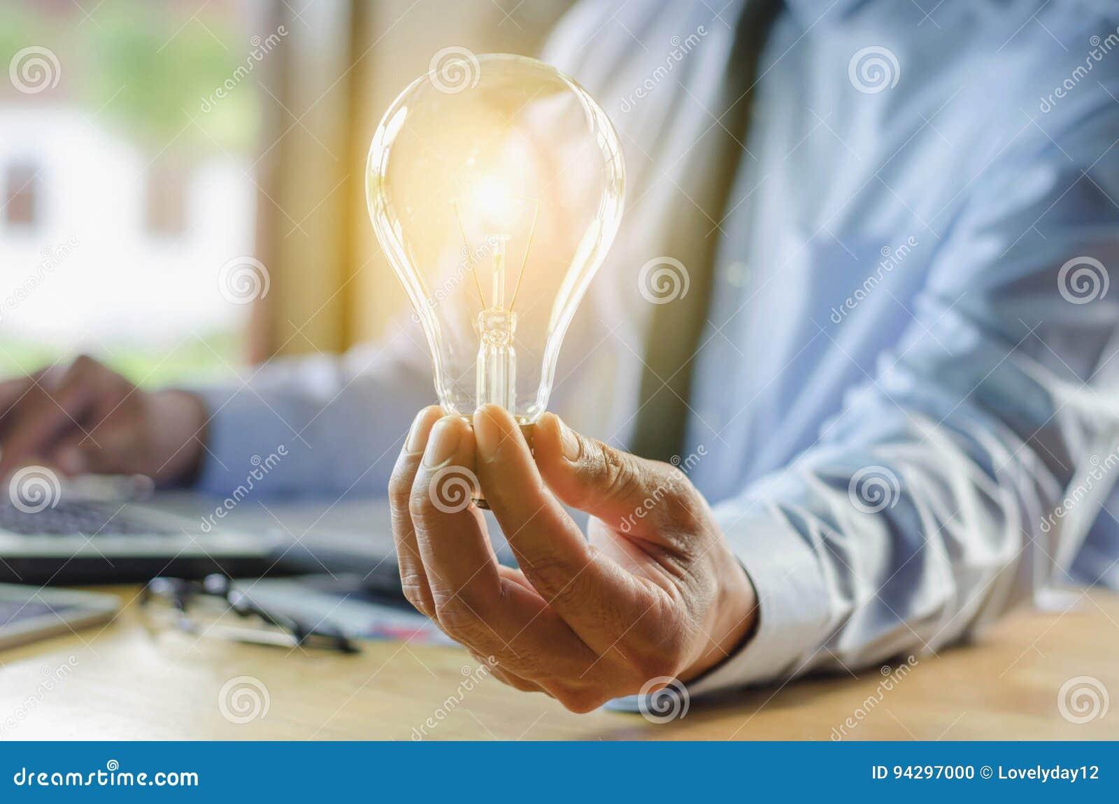 Hombre de negocios que sostiene la bombilla, idea del concepto con la innovación