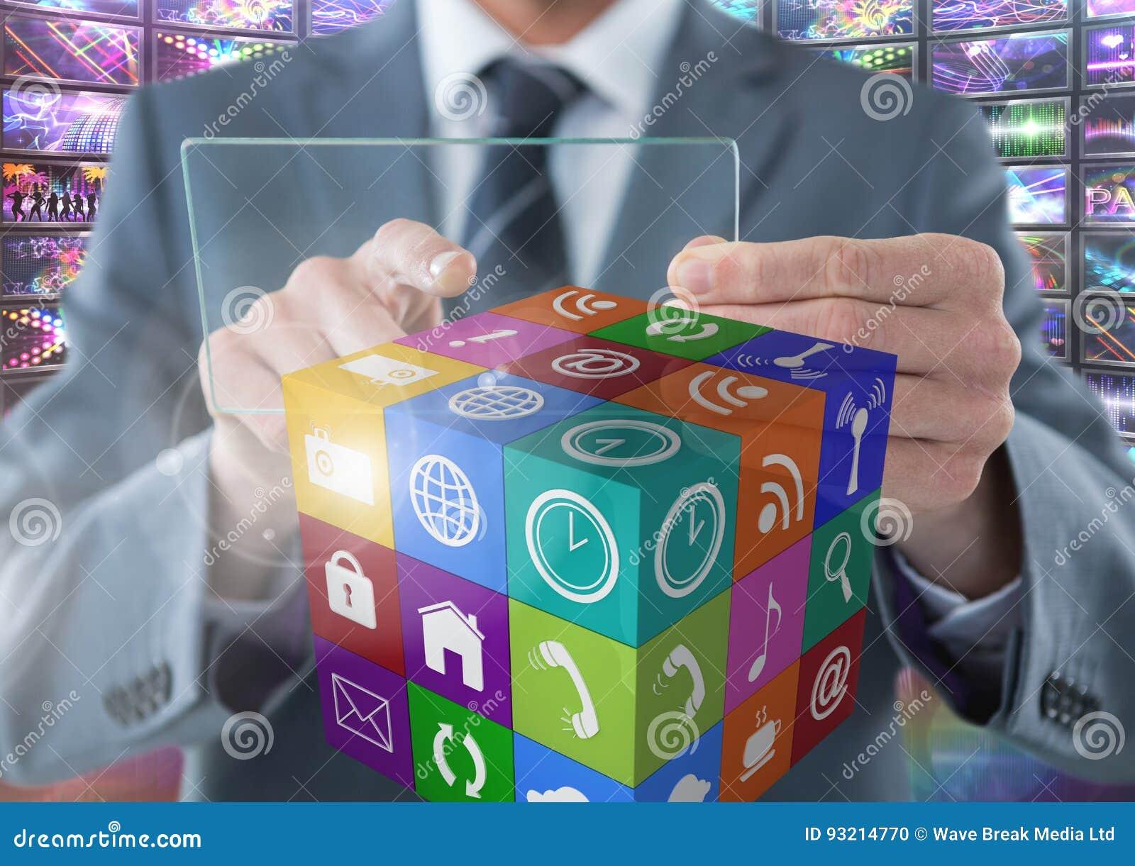 Hombre de negocios que sostiene la pantalla de cristal con los apps con representaciones visuales coloridas de las pantallas