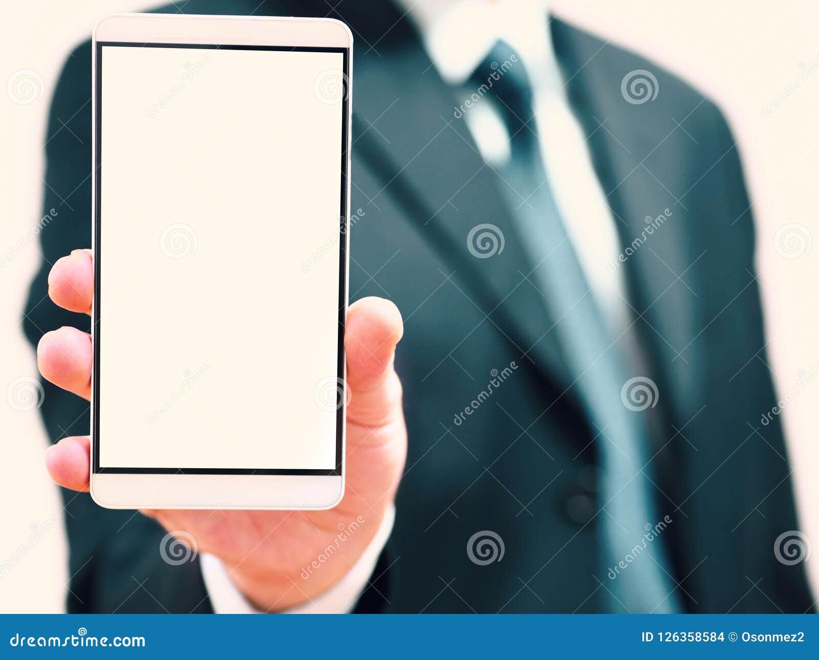 Hombre de negocios que sostiene un teléfono en su mano teléfono elegante con la pantalla en blanco para las ideas del concepto