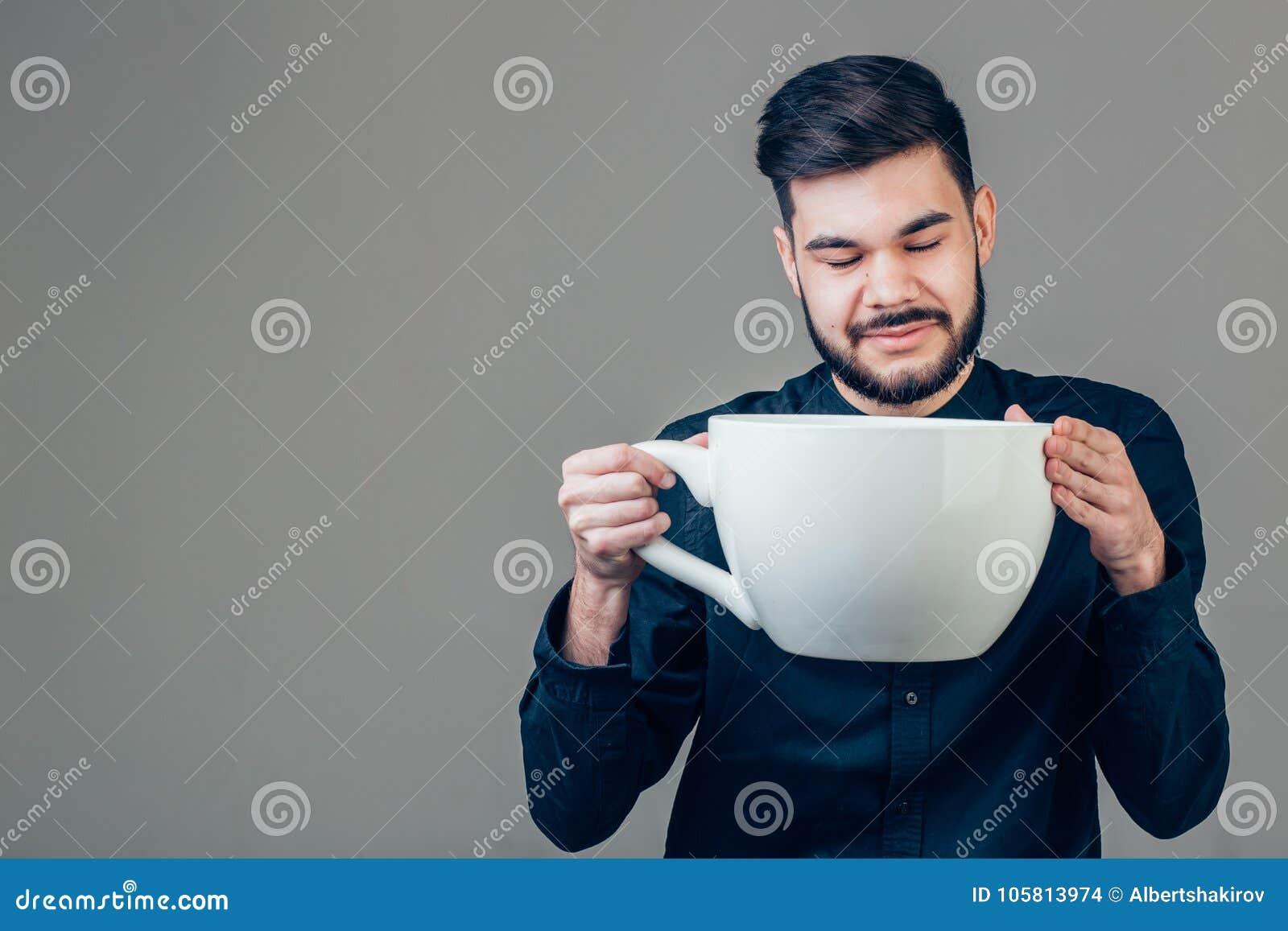 Hombre de negocios que sostiene una taza enorme y de gran tamaño divertida de café sólo en cafeína