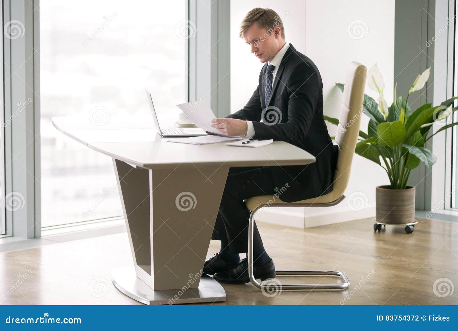 Hombre de negocios que trabaja con el ordenador portátil y el papel en el escritorio moderno