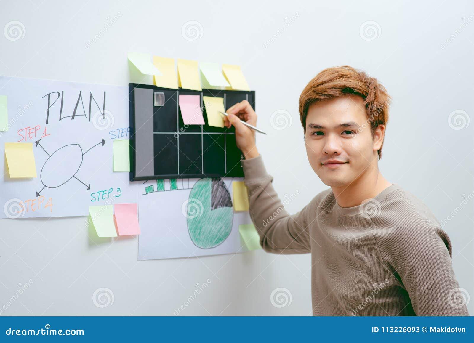 Hombre de negocios que trabaja en la oficina con las pilas de libros y de papeles