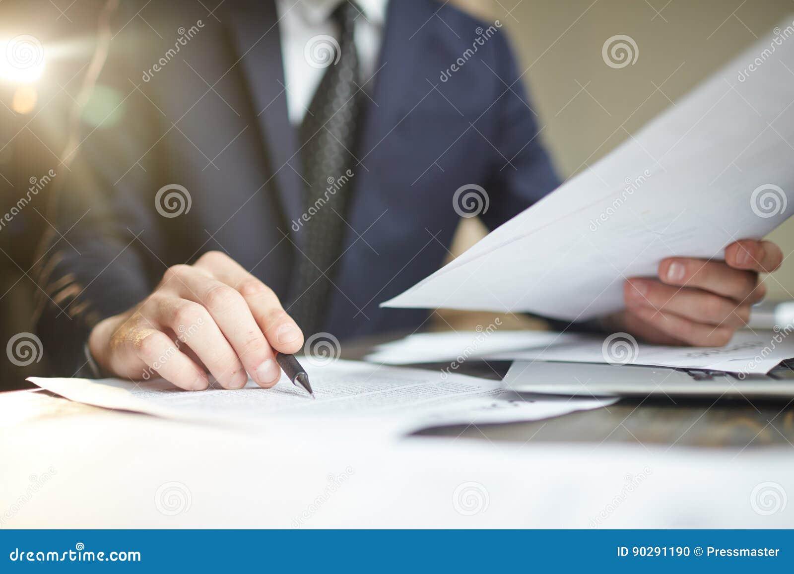 Hombre de negocios Reviewing Paperwork Closeup
