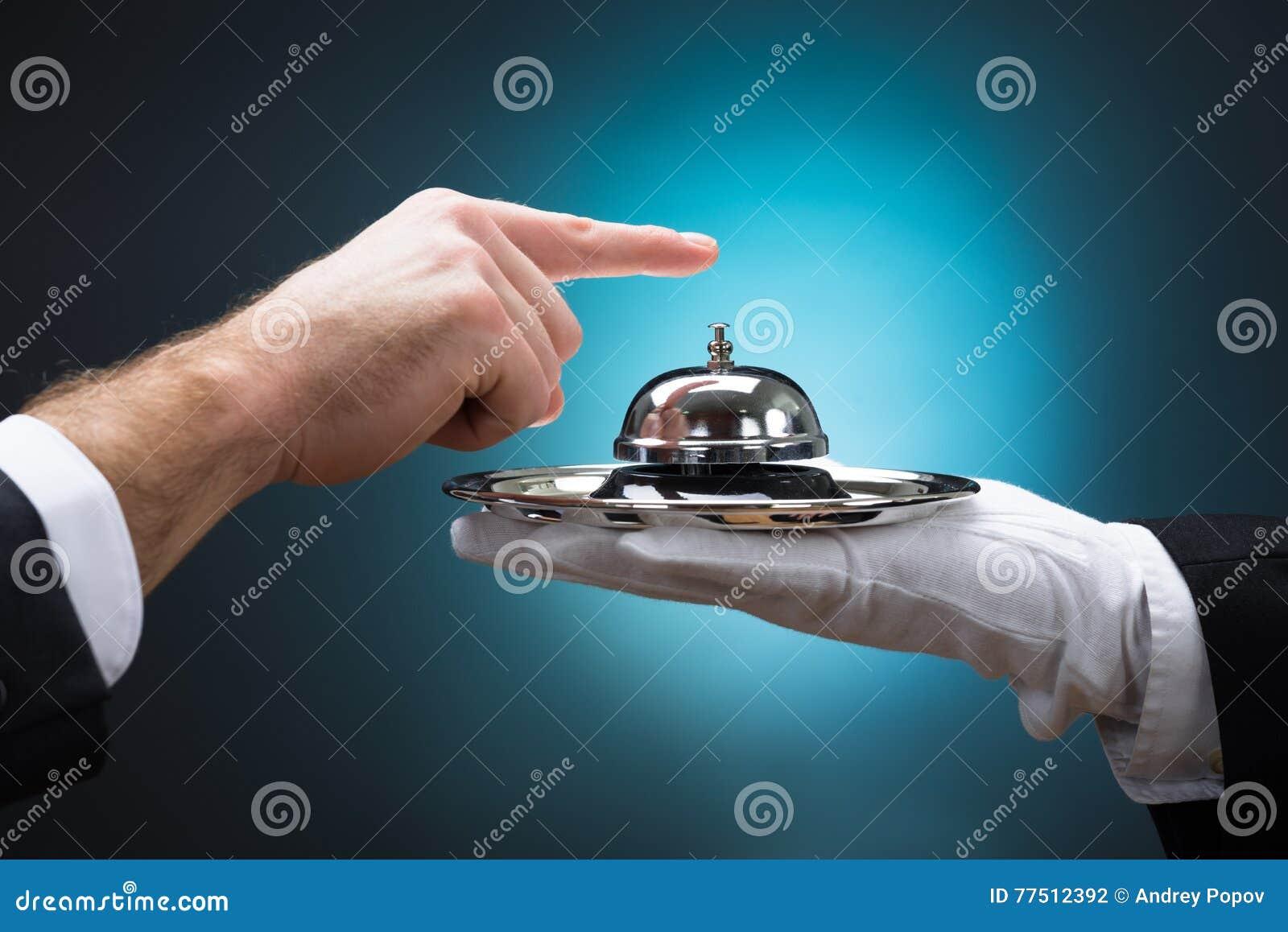 Hombre de negocios Ringing In Service Bell sostenida por el botones
