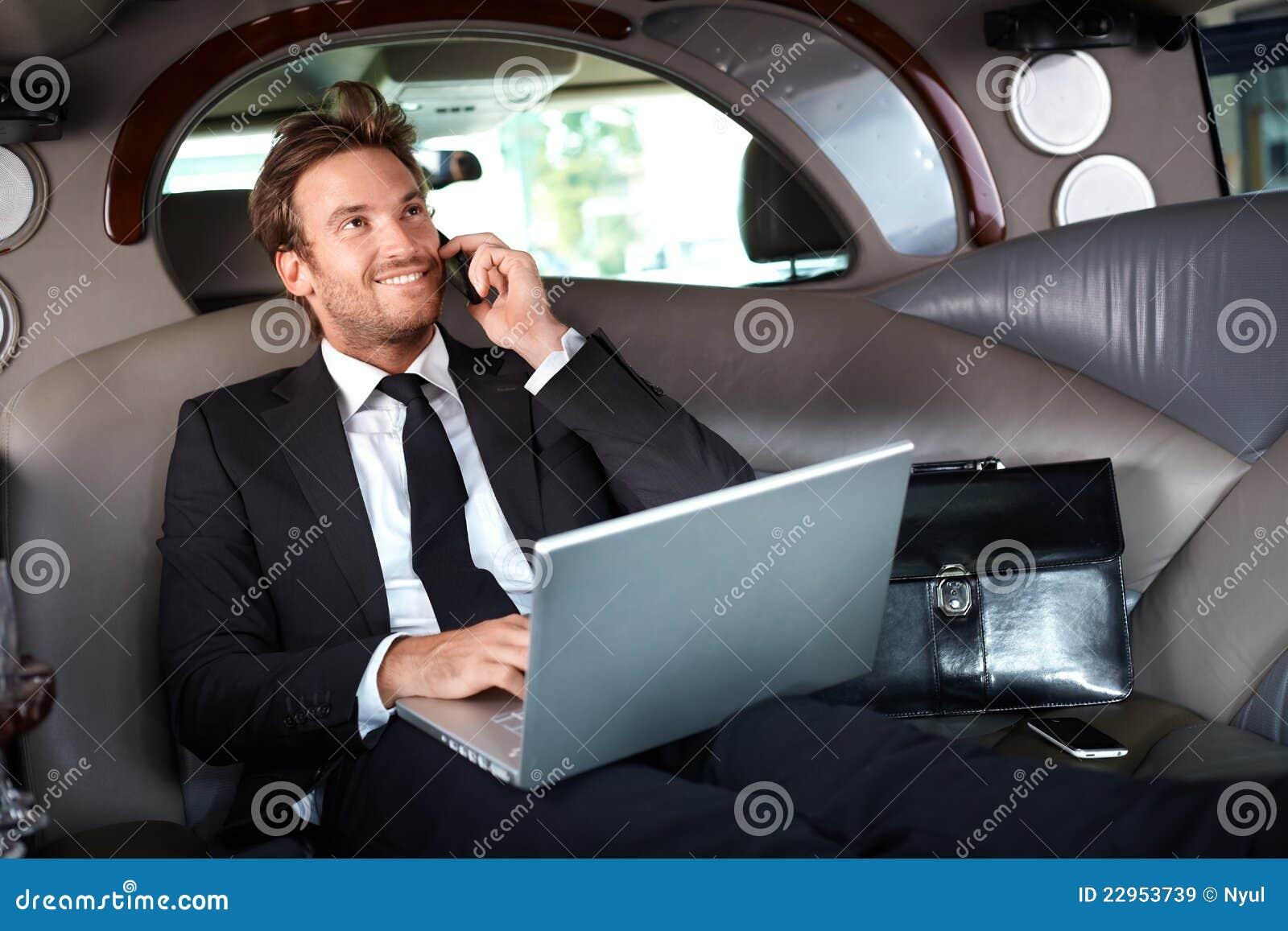Hombre de negocios sonriente en el funcionamiento de lujo del coche