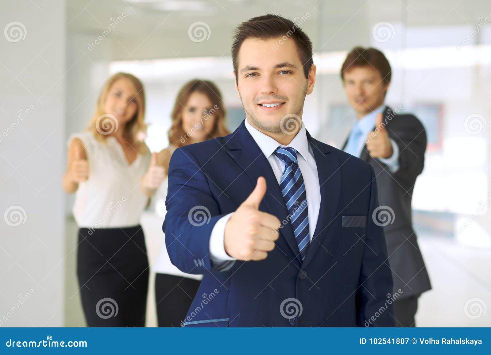 Hombre de negocios sonriente en oficina con los colegas en el fondo Pulgares para arriba
