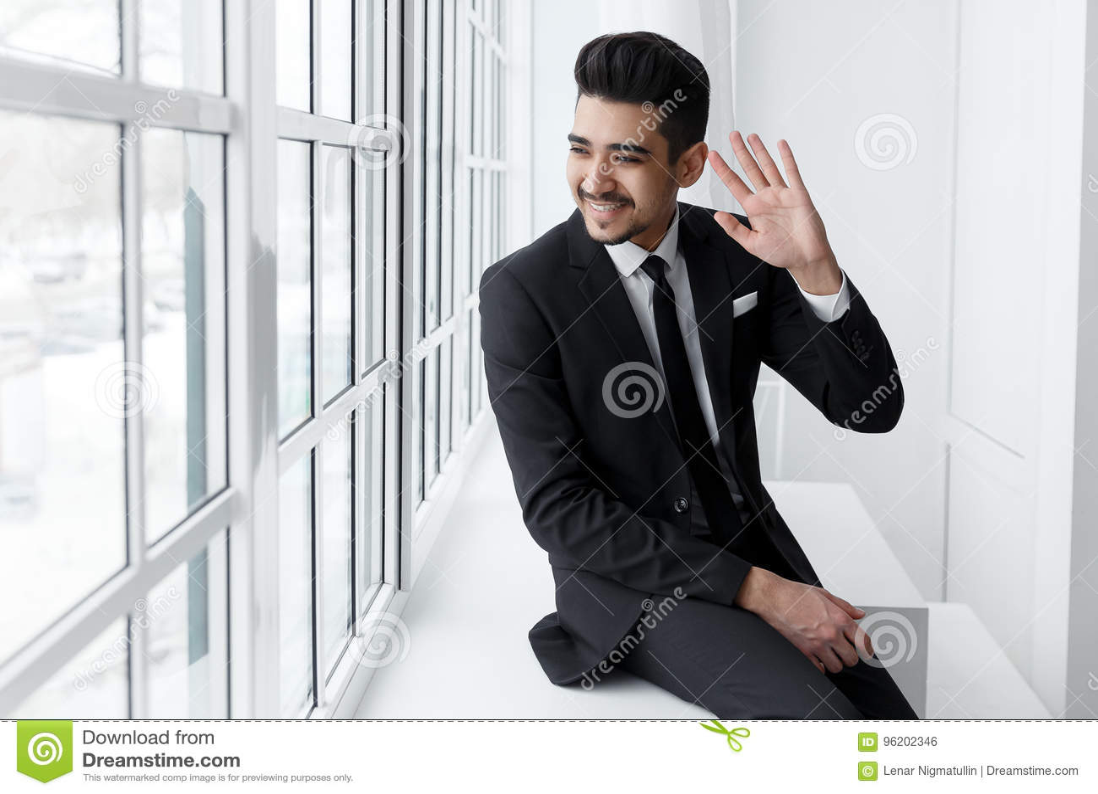Hombre de negocios sonriente joven que se sienta en alféizar