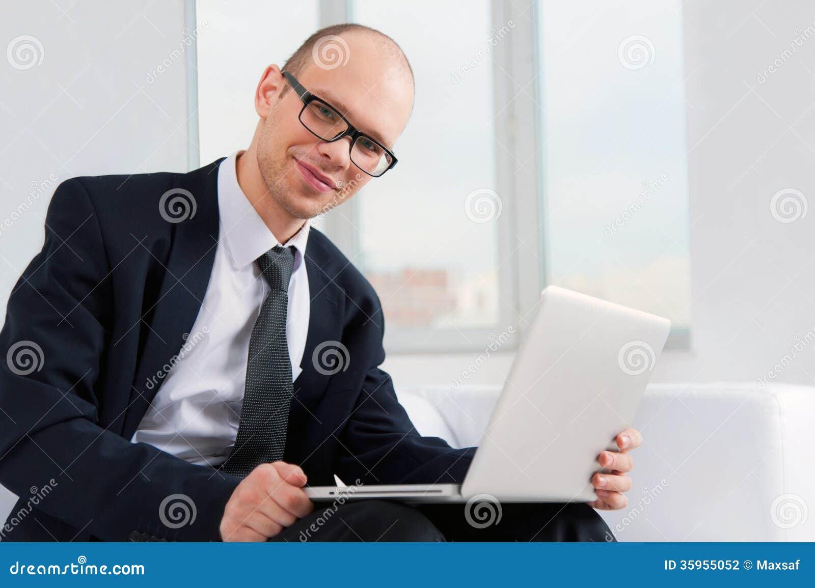 Hombre de negocios sonriente joven que se sienta en el sofá con el ordenador portátil