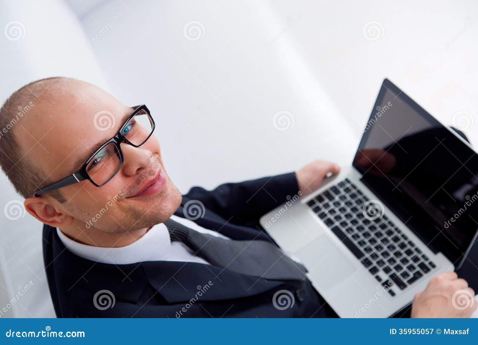 Hombre de negocios sonriente joven usando el ordenador portátil