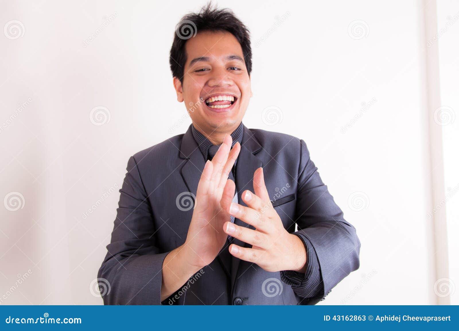 Hombre de negocios sonriente que aplaude sus manos
