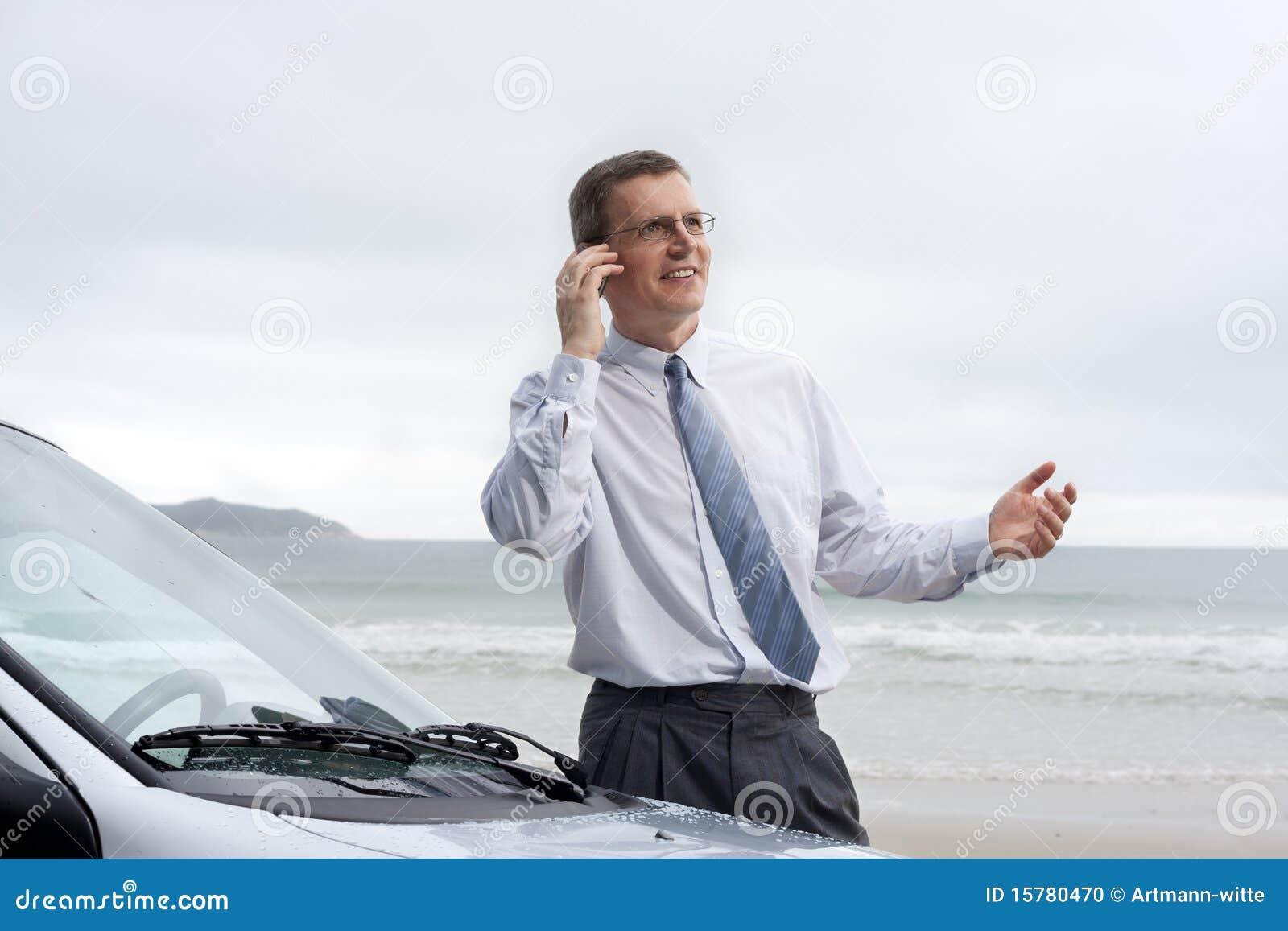 Hombre de negocios sonriente que habla en el teléfono celular