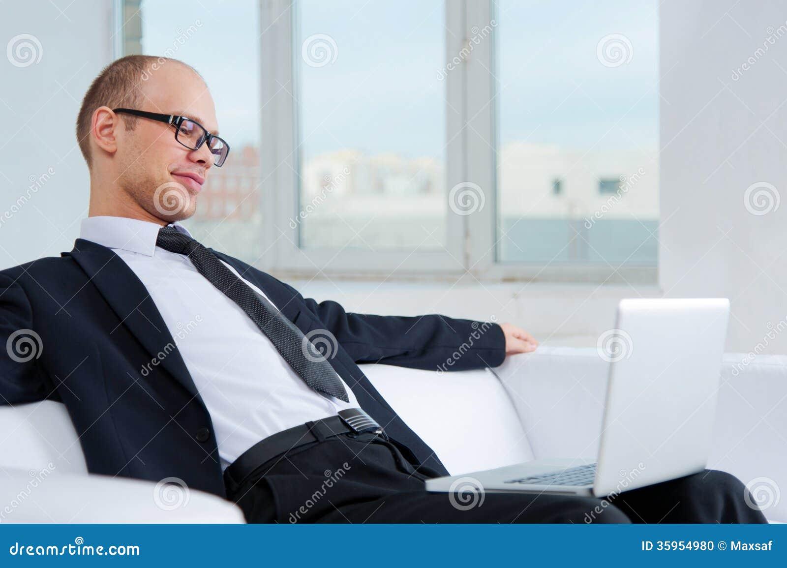 Hombre de negocios sonriente que se sienta en el sofá con el ordenador portátil
